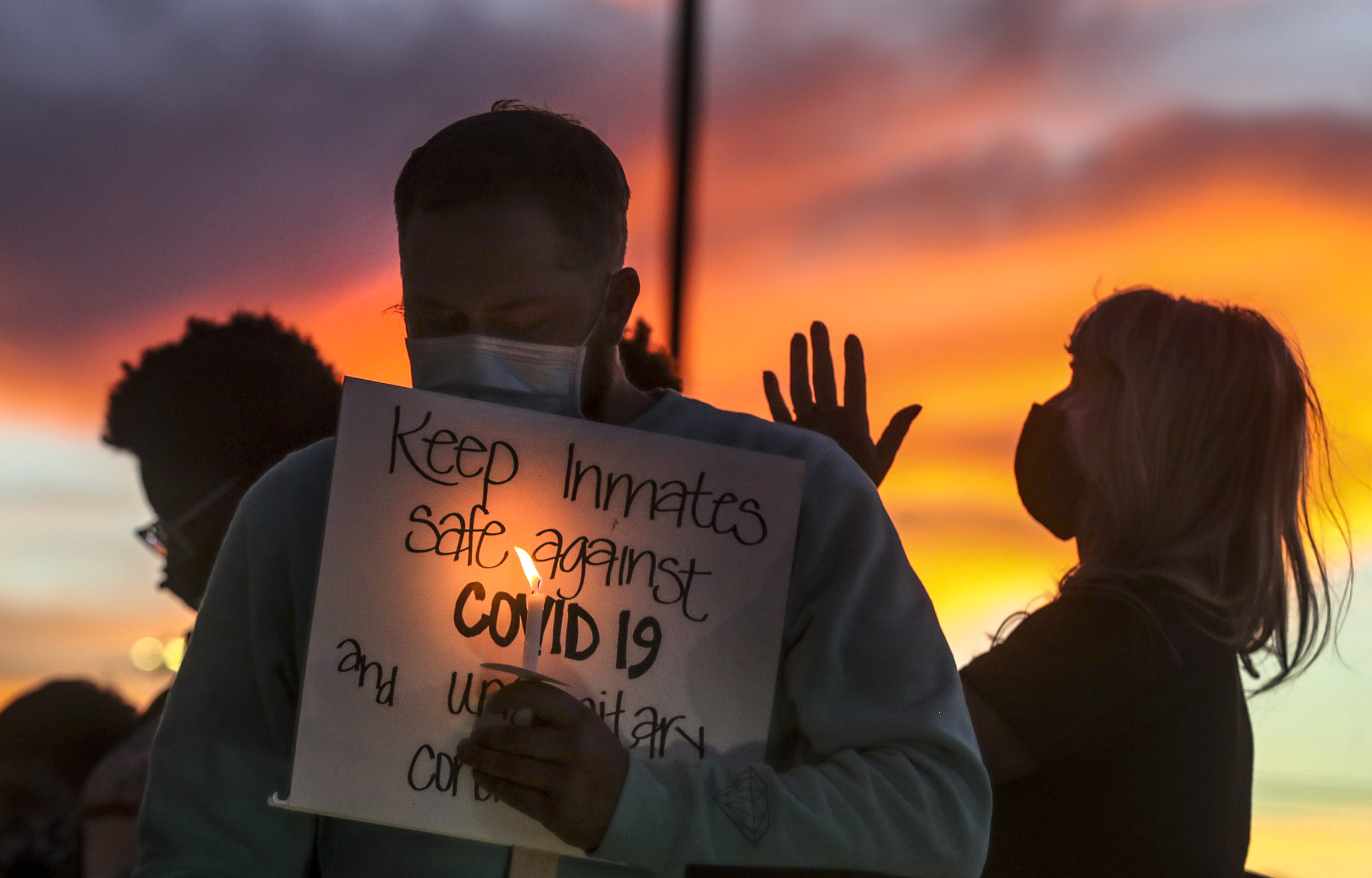 Family members of inmates incarcerated in the Utah Department of Corrections' prison system hold candles and say a prayer following a rally outside the Department of Corrections office in Draper on Tuesday, Oct. 13, 2020. The group was there to share concerns about the department's handling of the COVID-19 outbreak.