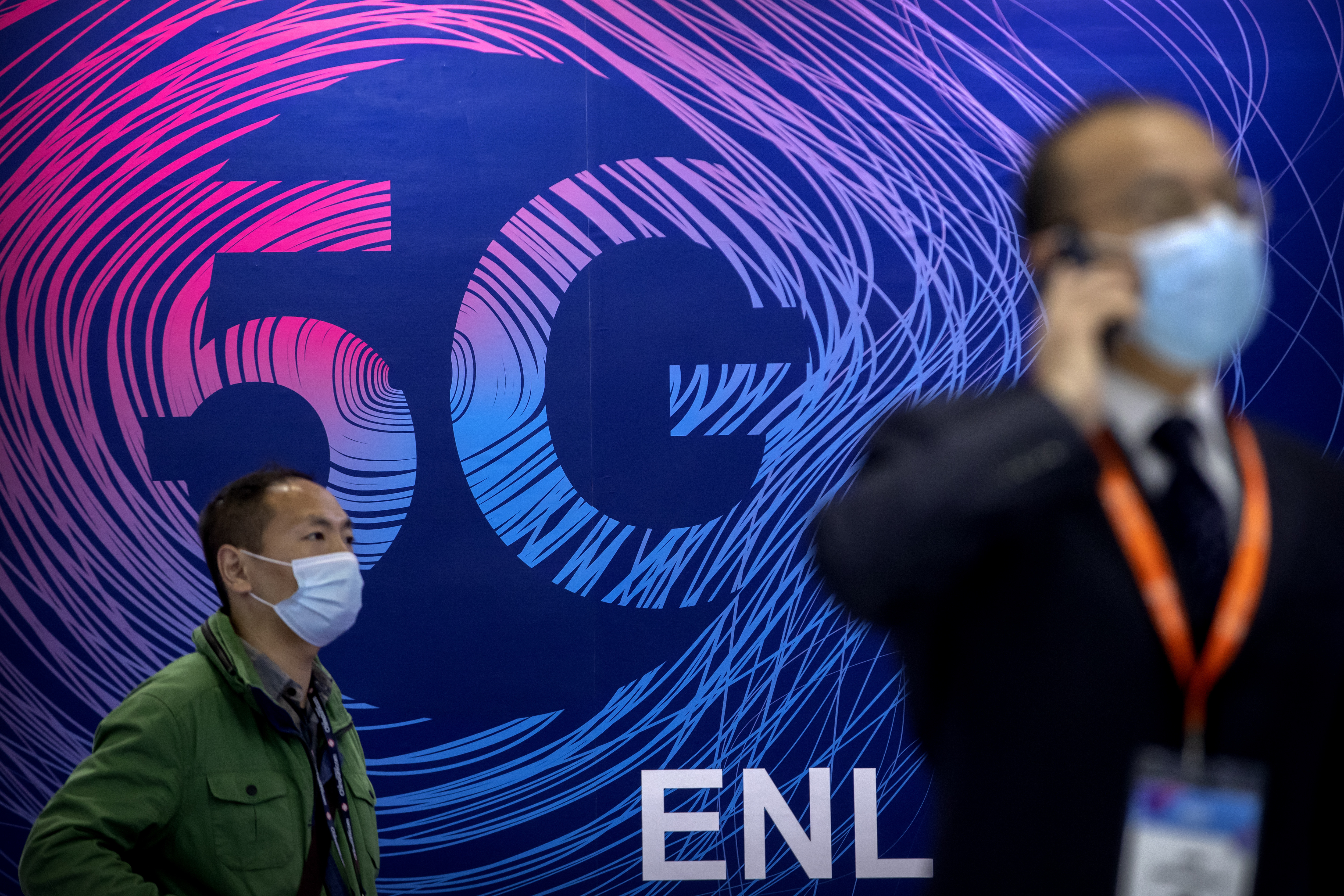 Attendees wearing face masks to protect against the coronavirus walk past an advertisement for 5G cellular technology at the PT Expo in Beijing, Wednesday, Oct. 14, 2020.