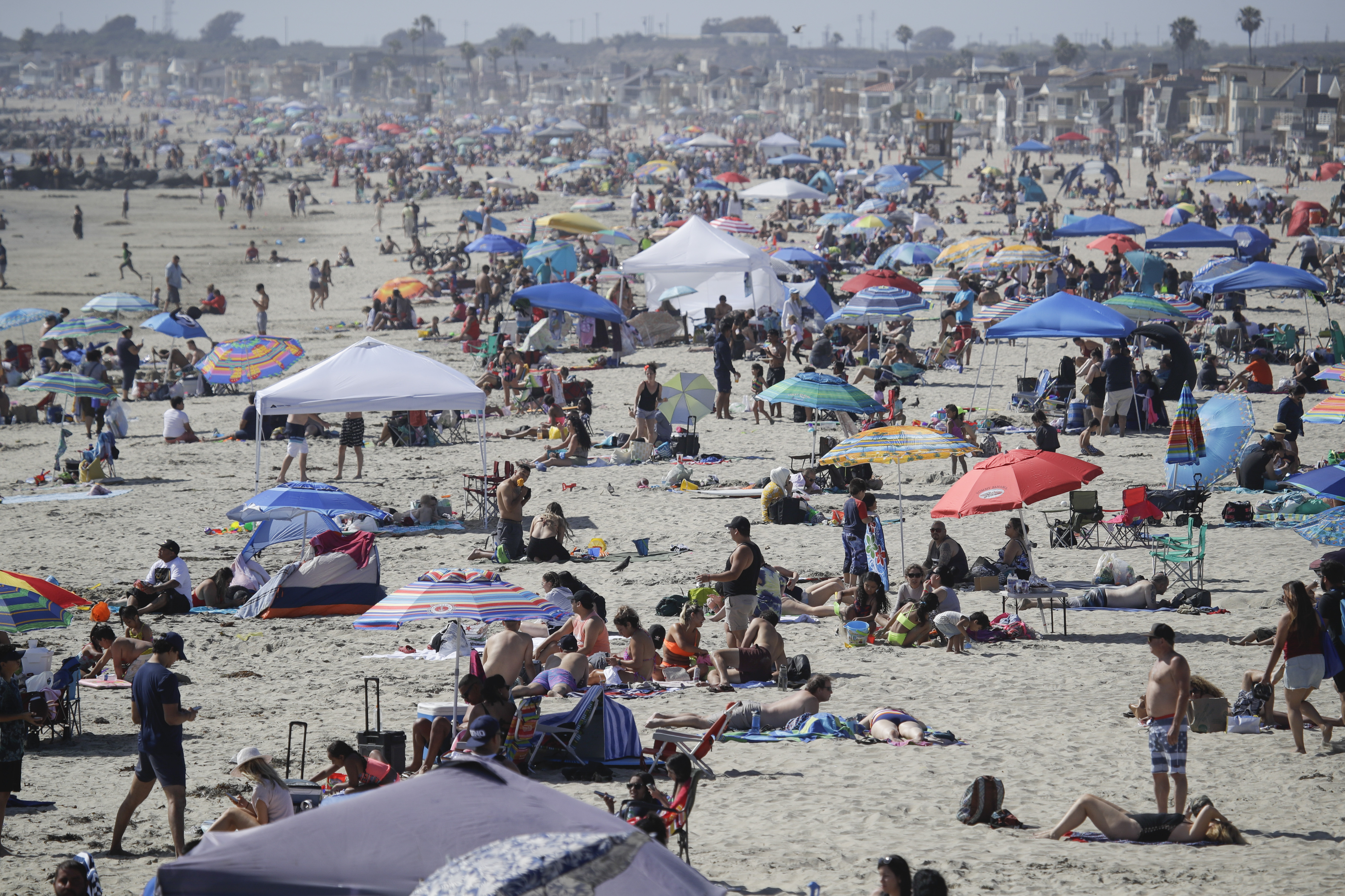 This May 24, 2020, file photo, shows visitors gathering on the beach in Newport Beach, Calif., during the coronavirus outbreak.
