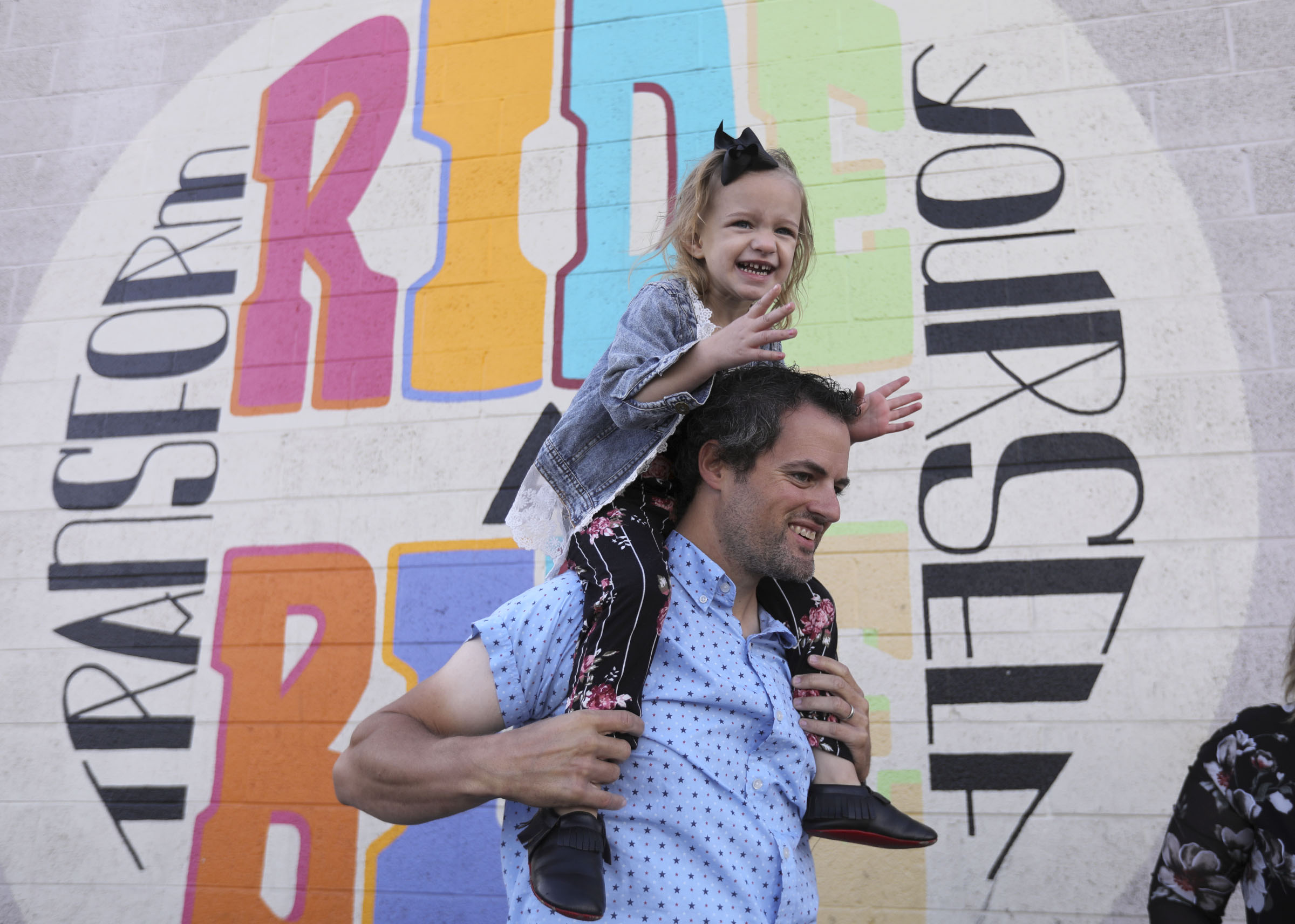 Mike West holds daughter Cozette West on his shoulders during a press conference about how biking has become their family's primary mode of transportation outside of the Bicycle Collective in Salt Lake City on Wednesday, Oct. 14, 2020. Data shows there has been an increase in walking and biking during the COVID-19 pandemic.