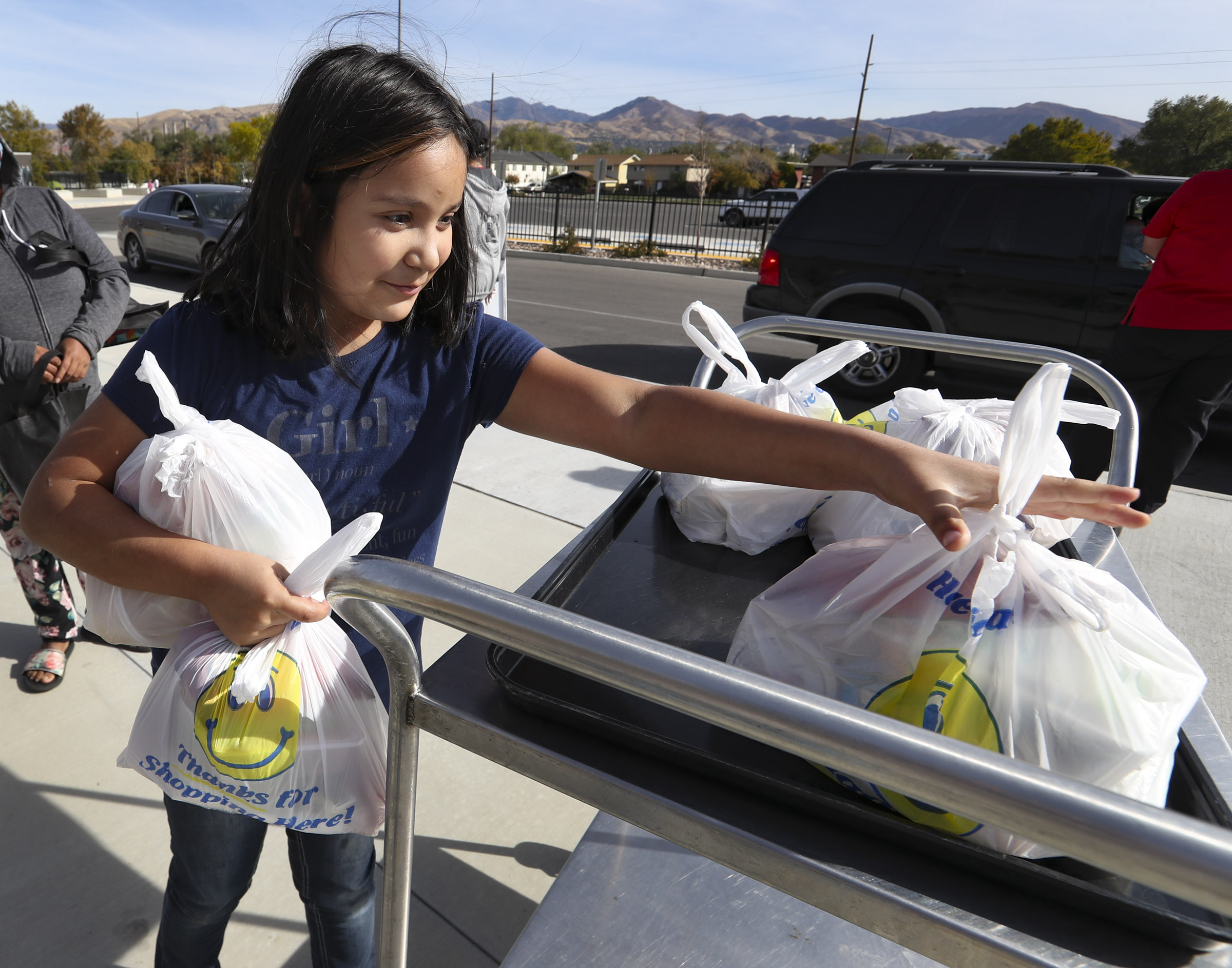 Paola Hernandez, a third grader at Edison Elementary School, gets some grab-and-go lunches for her family at the school in Salt Lake City on Thursday, Oct. 15, 2020. To help meet the food need of students, the Salt Lake Education Foundation with the help of Smith's Food & Drug are providing 5,200 meals to students. The Salt Lake City School District's child nutrition department will give out these additional meals at Edison and Escalante elementary schools. The donation from Smith's Food & Drug Stores supports the company's Zero Hunger | Zero Waste plan which is aiming to end hunger in communities and eliminate waste across the company by 2025.