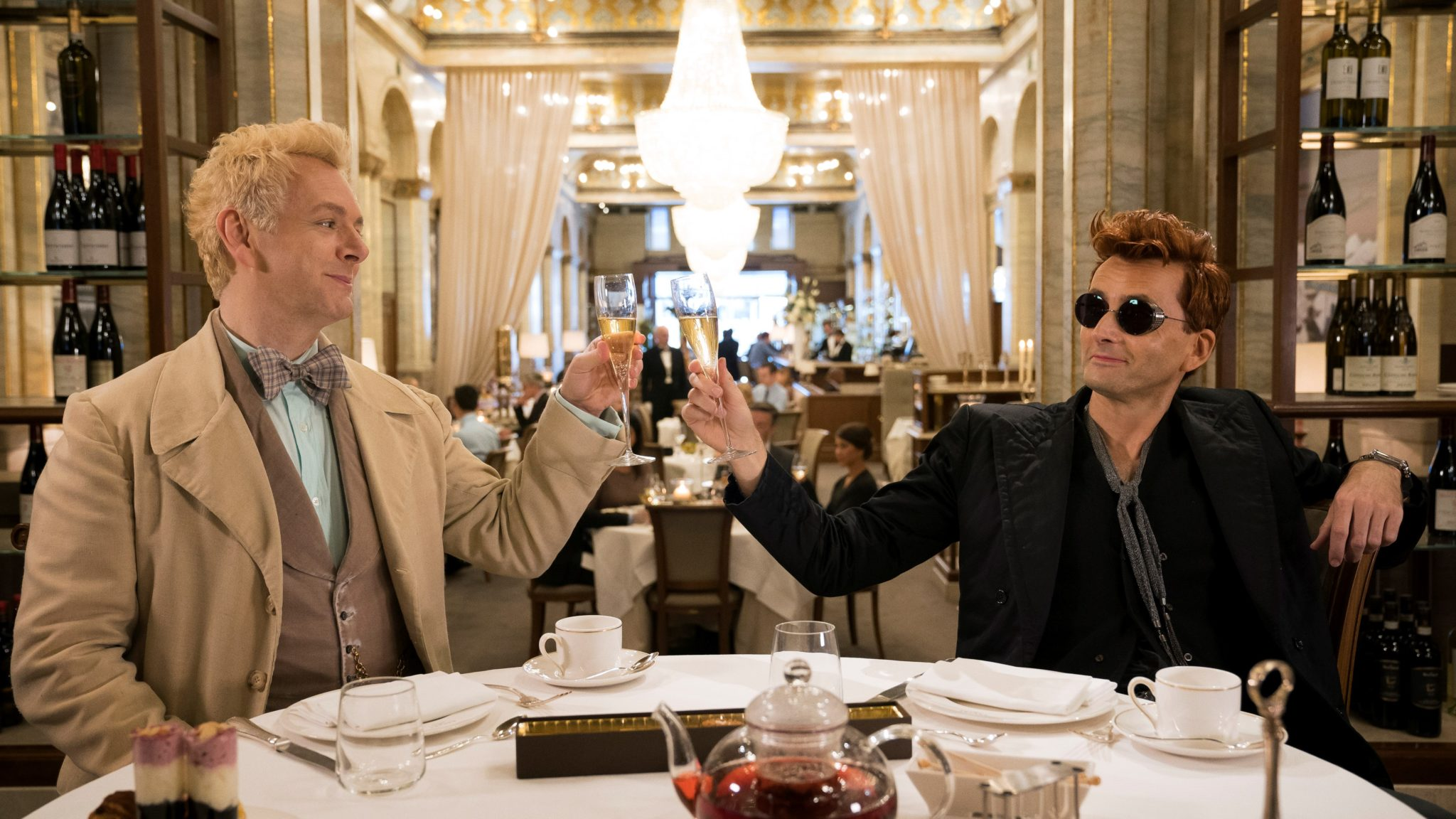 in the middle of a crowded restaurant, Aziraphale, dressed in lighter colors, and Crowley, dressed in mostly black, have a toast on Good Omens