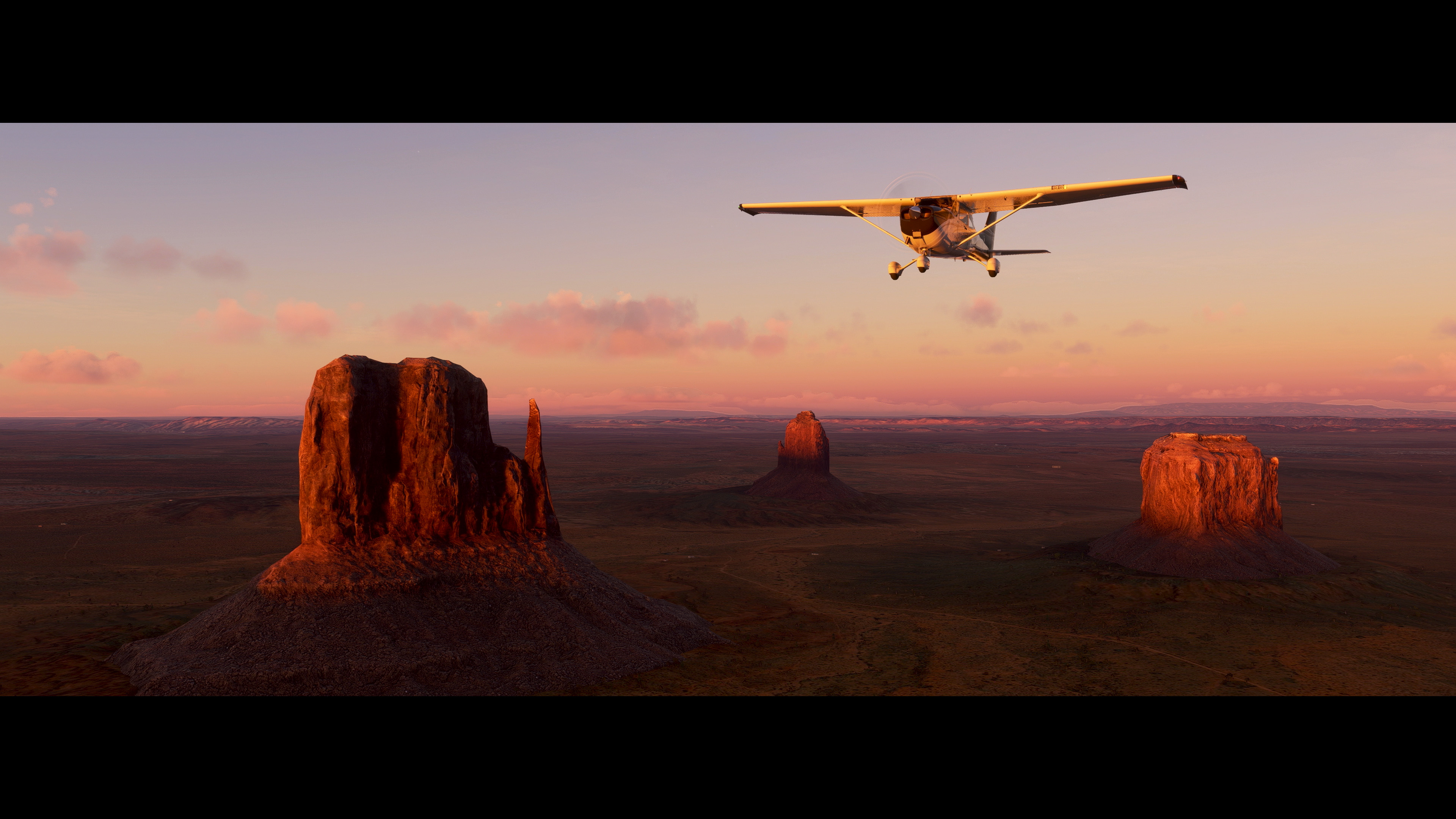 A plane flies over Arizona's Monument Valley in a screenshot from Microsoft Flight Simulator