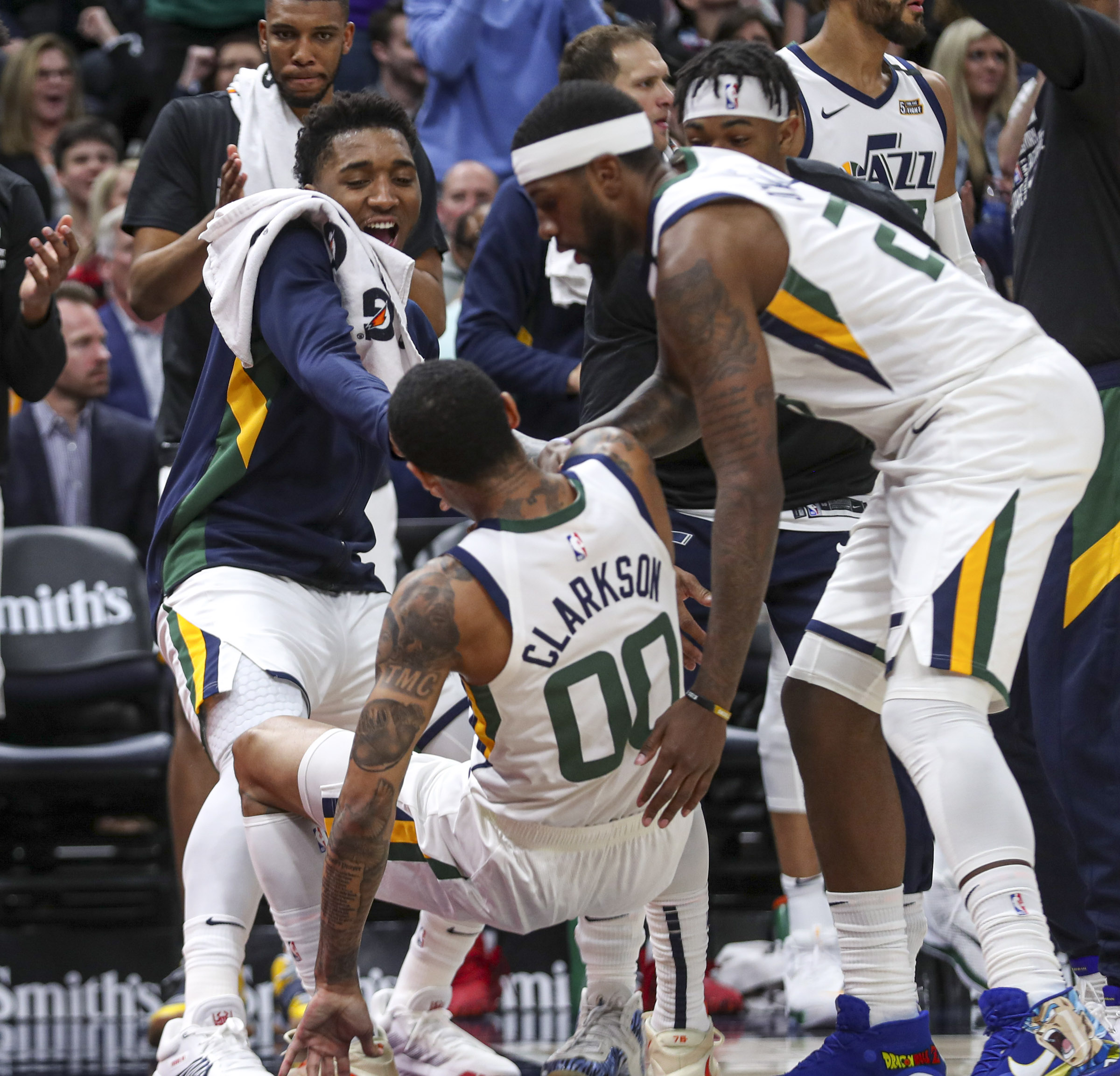 犹他爵士 guard Donovan Mitchell (45), left, 和 犹他爵士 forward Royce O'Neale (23) leap from the bench to help up 犹他爵士 guard Jordan Clarkson (00) after was fouled during the Houston Rockets at 犹他爵士 NBA basketball game at Vivint Arena in Salt Lake City on Saturday, Feb. 22, 2020.