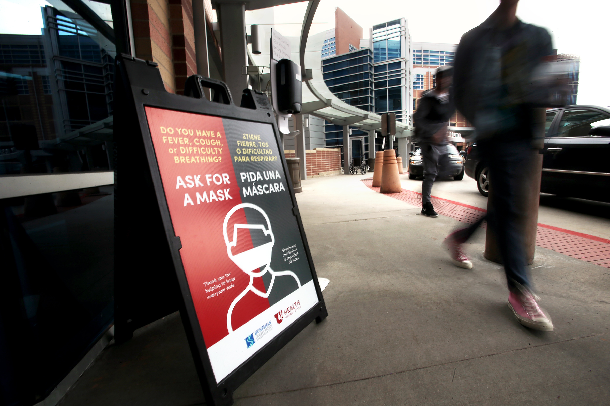 Visitors to the 犹他大学 Hospital in Salt Lake City walk past signs offering information about masks for those who are experiencing fever, cough or difficulty breathing on Monday, March 9, 2020. The hospital is preparing for potential COVID-19 patients.