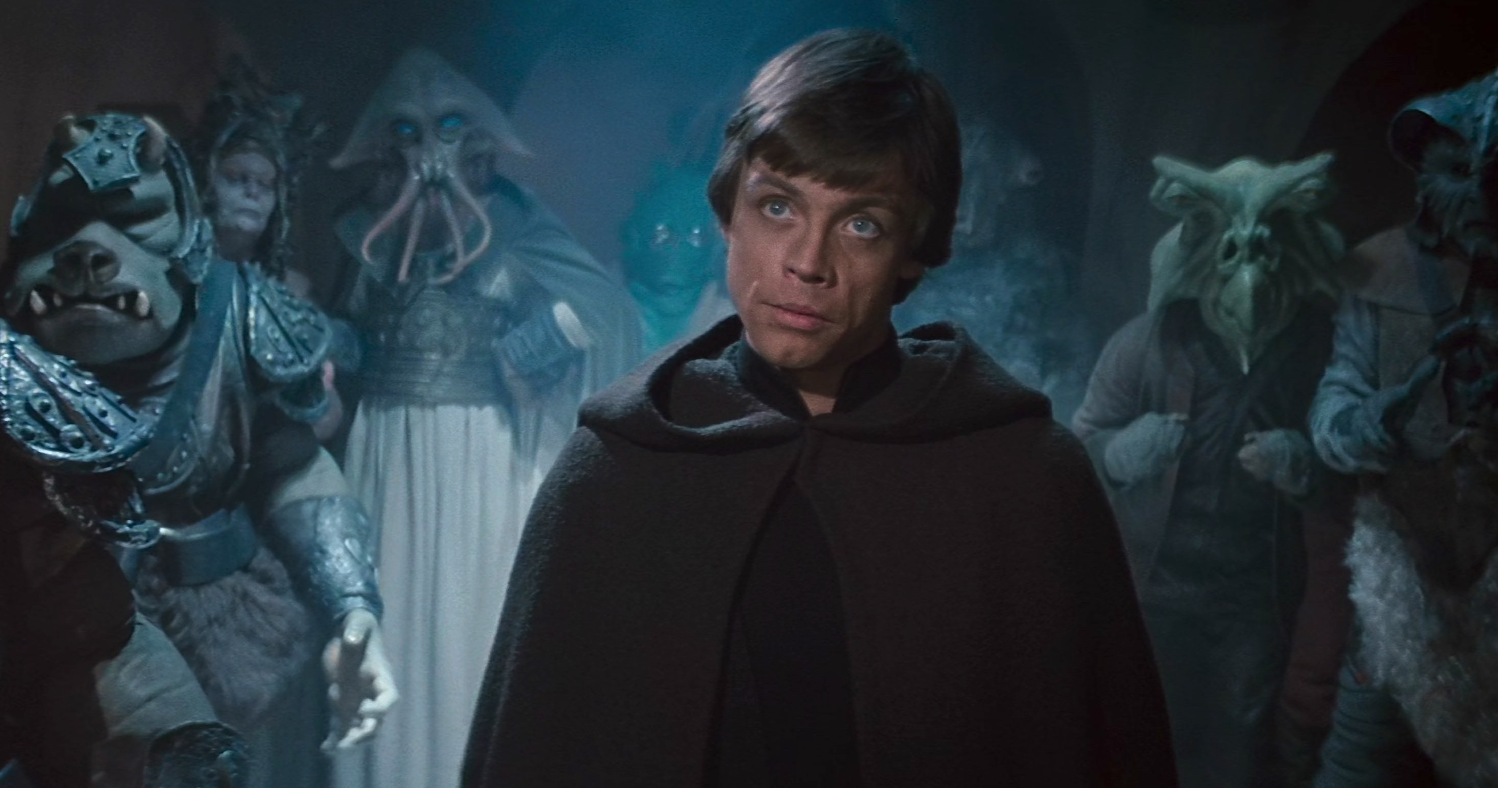 Luke Skywalker stands in Jabba's Palace with aliens behind him