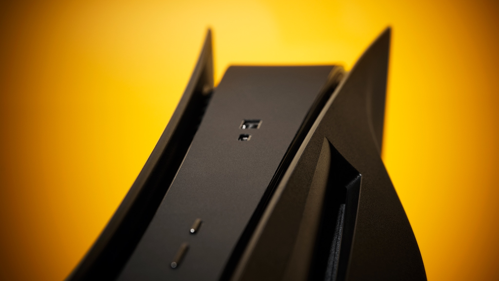 A close-up photo of an all-black PS5 with Dbrand faceplates