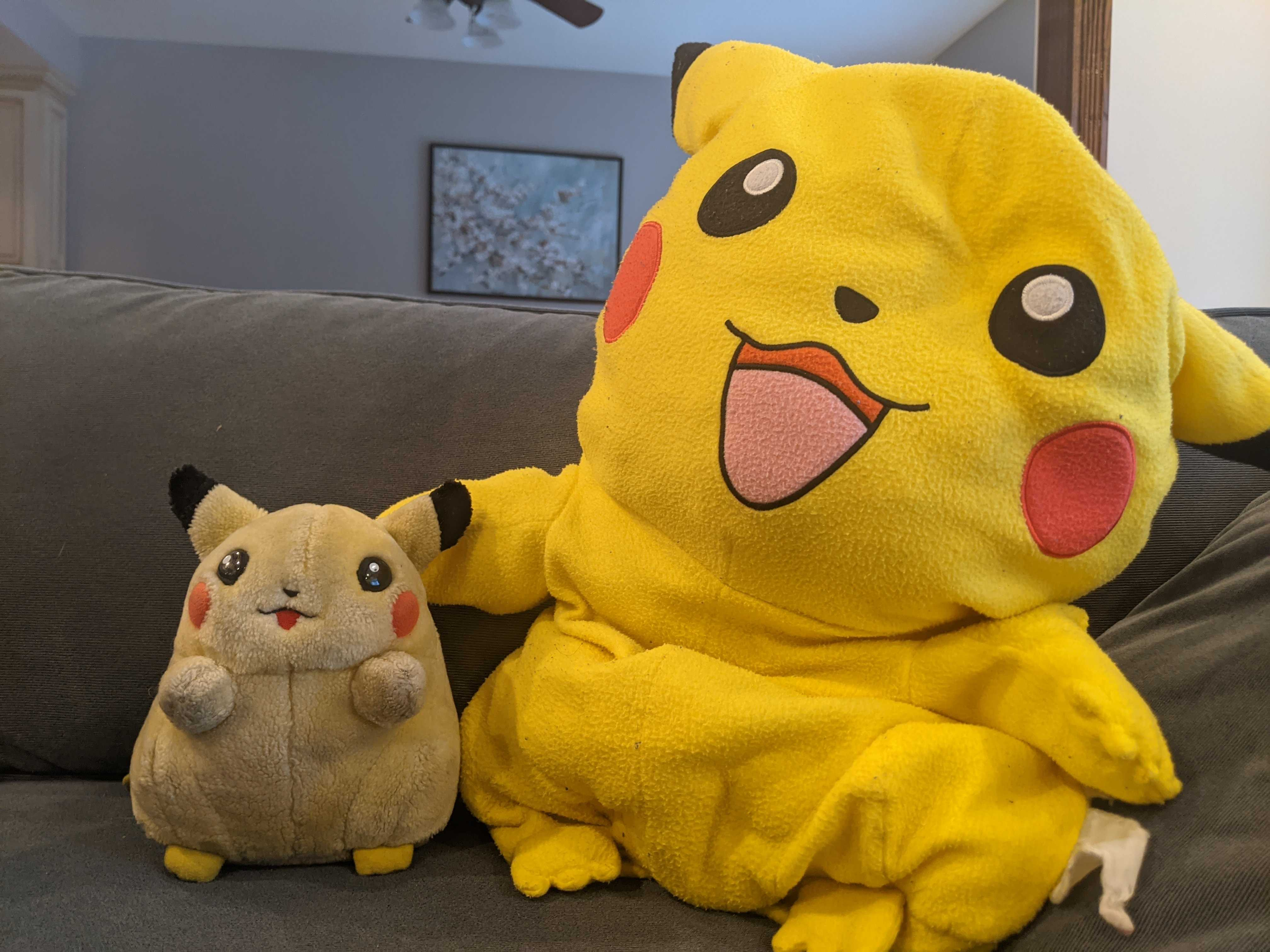 Two stuffed Pikachu sitting on a couch.