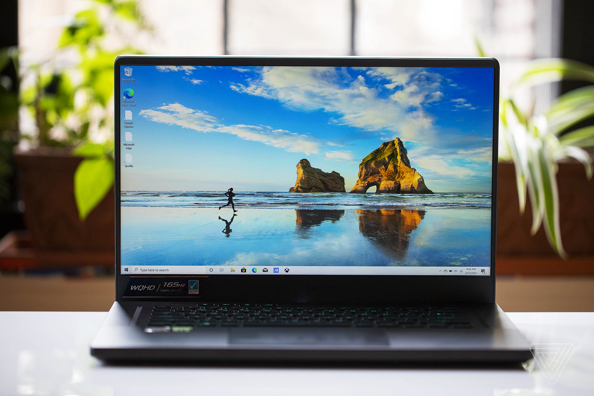 The Asus ROG Zephyrus G14 set on a table with two plants and a window in the background, open. The screen displays two rocks on a beach with a person running towards them across a body of water.