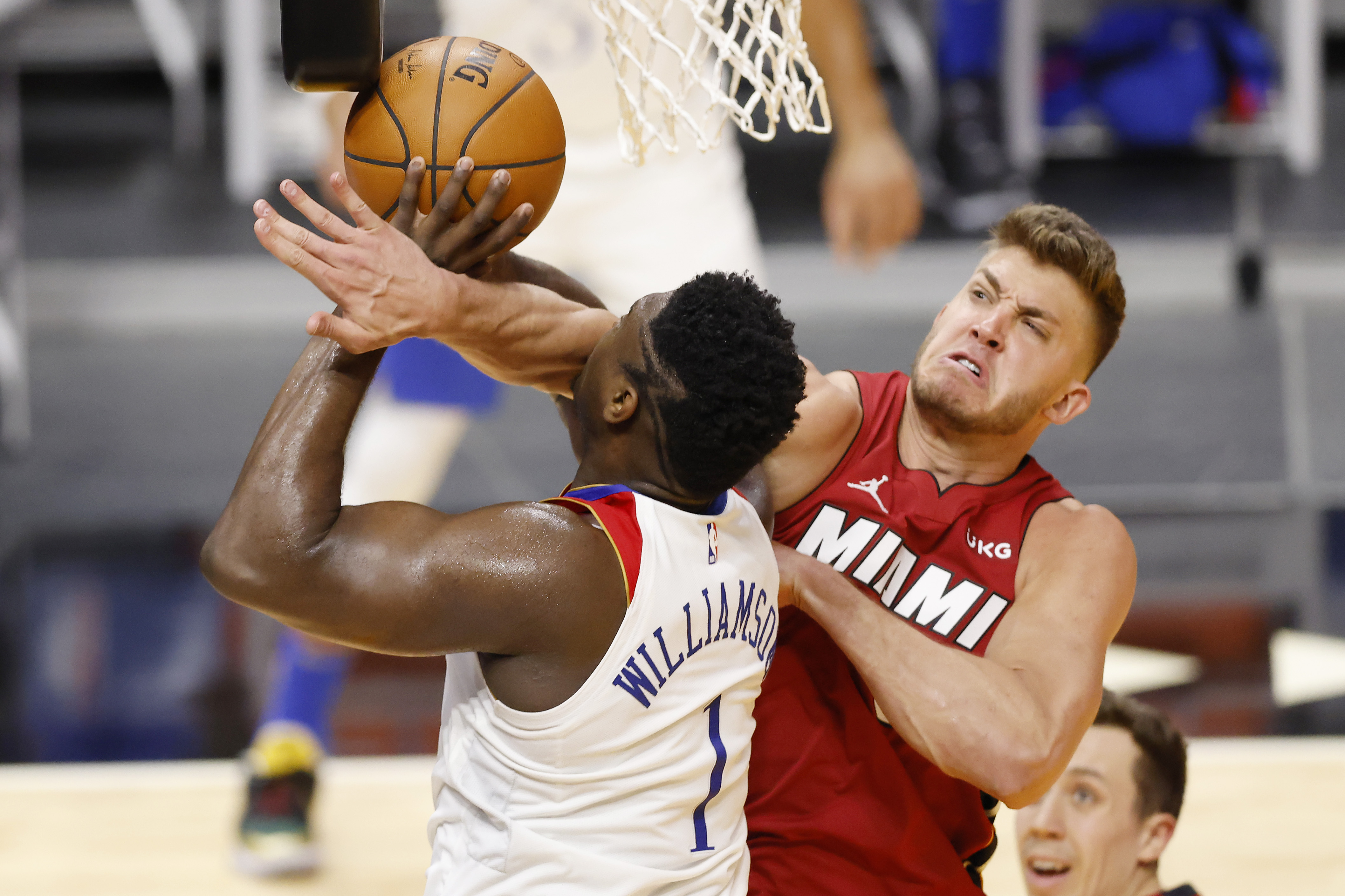 Zion Williamson of the New Orleans Pelicans goes up for a shot at the rim but gets fouled by Meyers Leonard of the Miami Heat