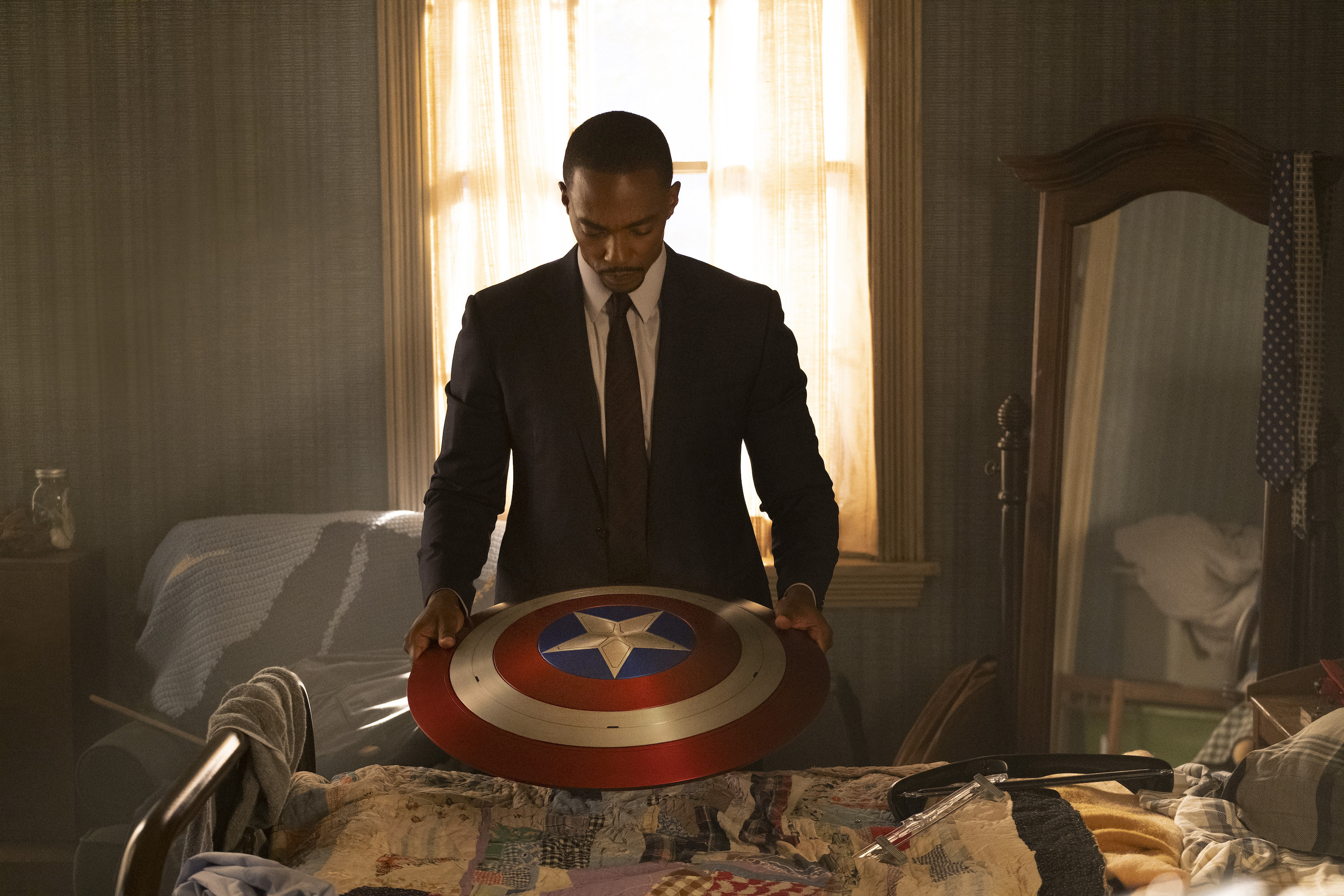 Sam Wilson (Anthony Mackie) stands in front of a window holding Captain America's shield thoughtfully in Falcon and the Winter Soldier