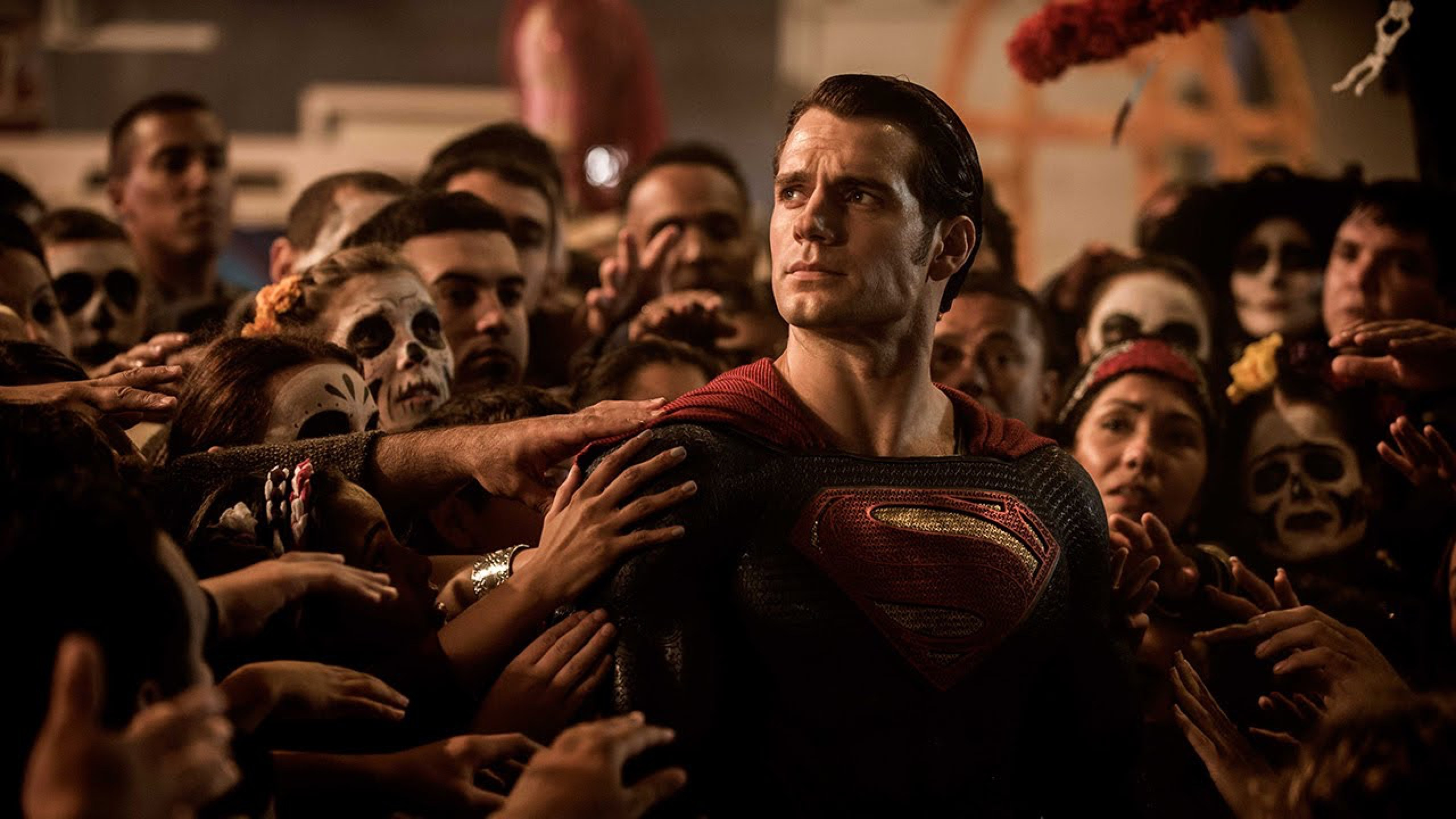 Superman (Henry Cavill) surrounded by worshipful people in face paint in Batman v Superman: Dawn of Justice