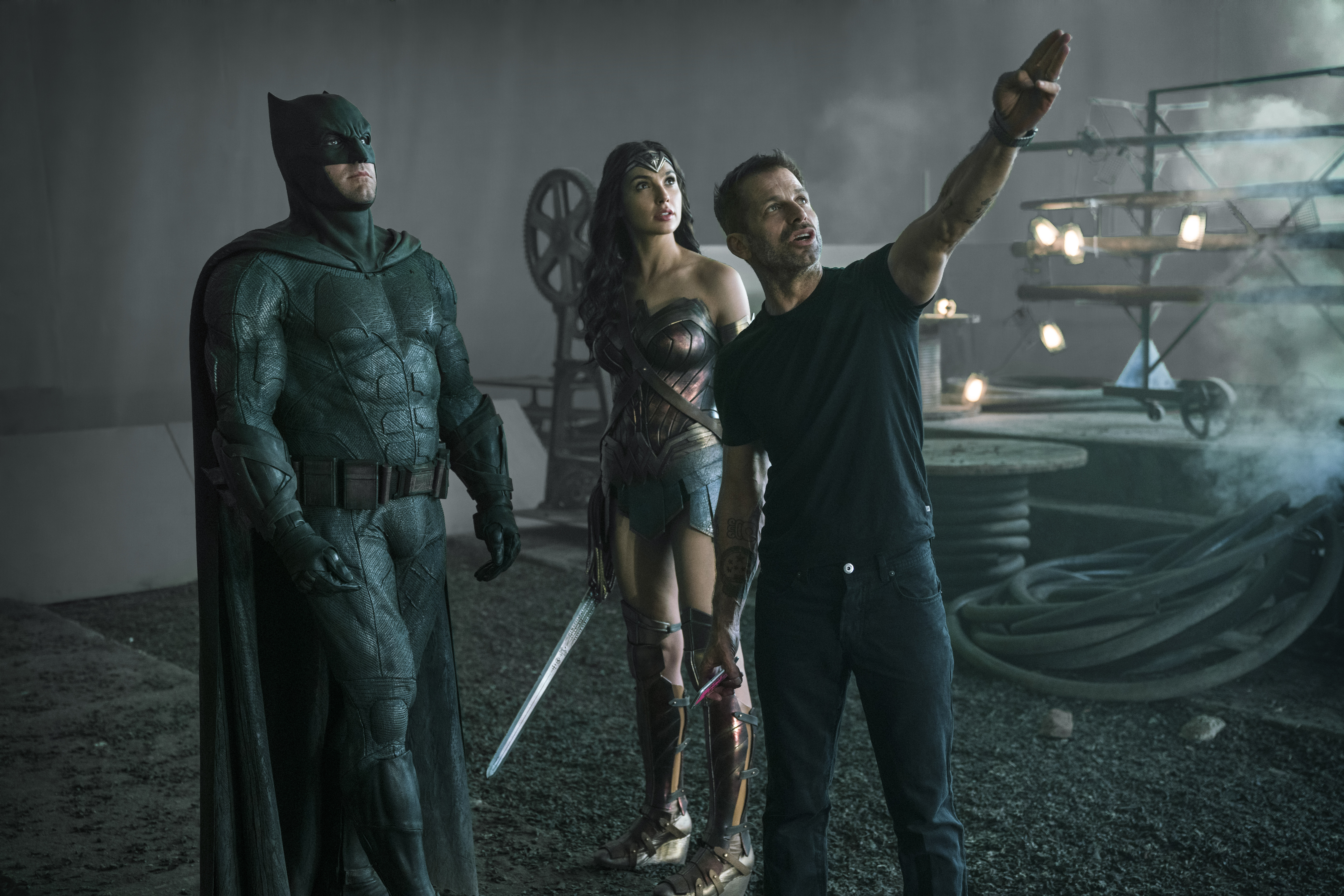 Batman, Wonder Woman, and Zack Snyder standing on the set of Justice League