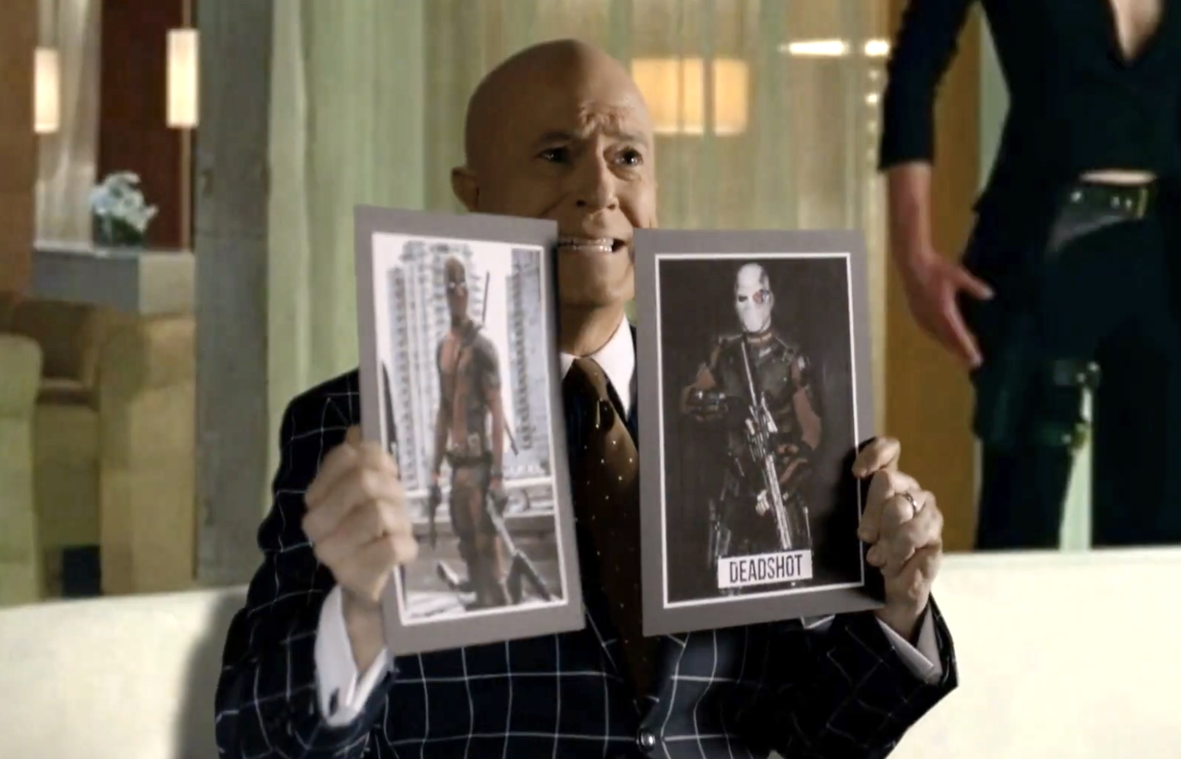 Stephen Colbert holds up pictures of Deadpool and Deadshot