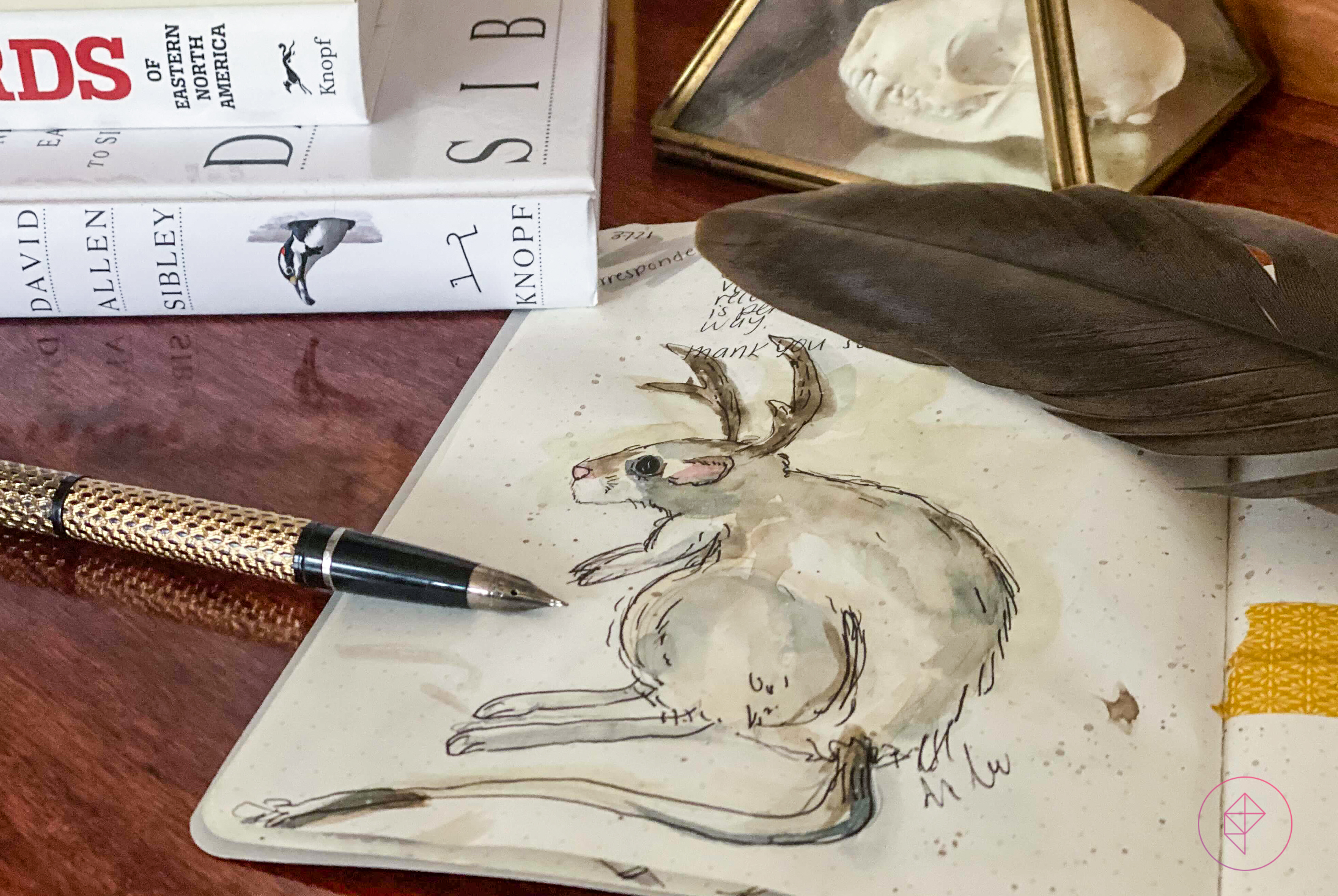 A watercolor painting of a rodent with horns, with a fountain pen next to it