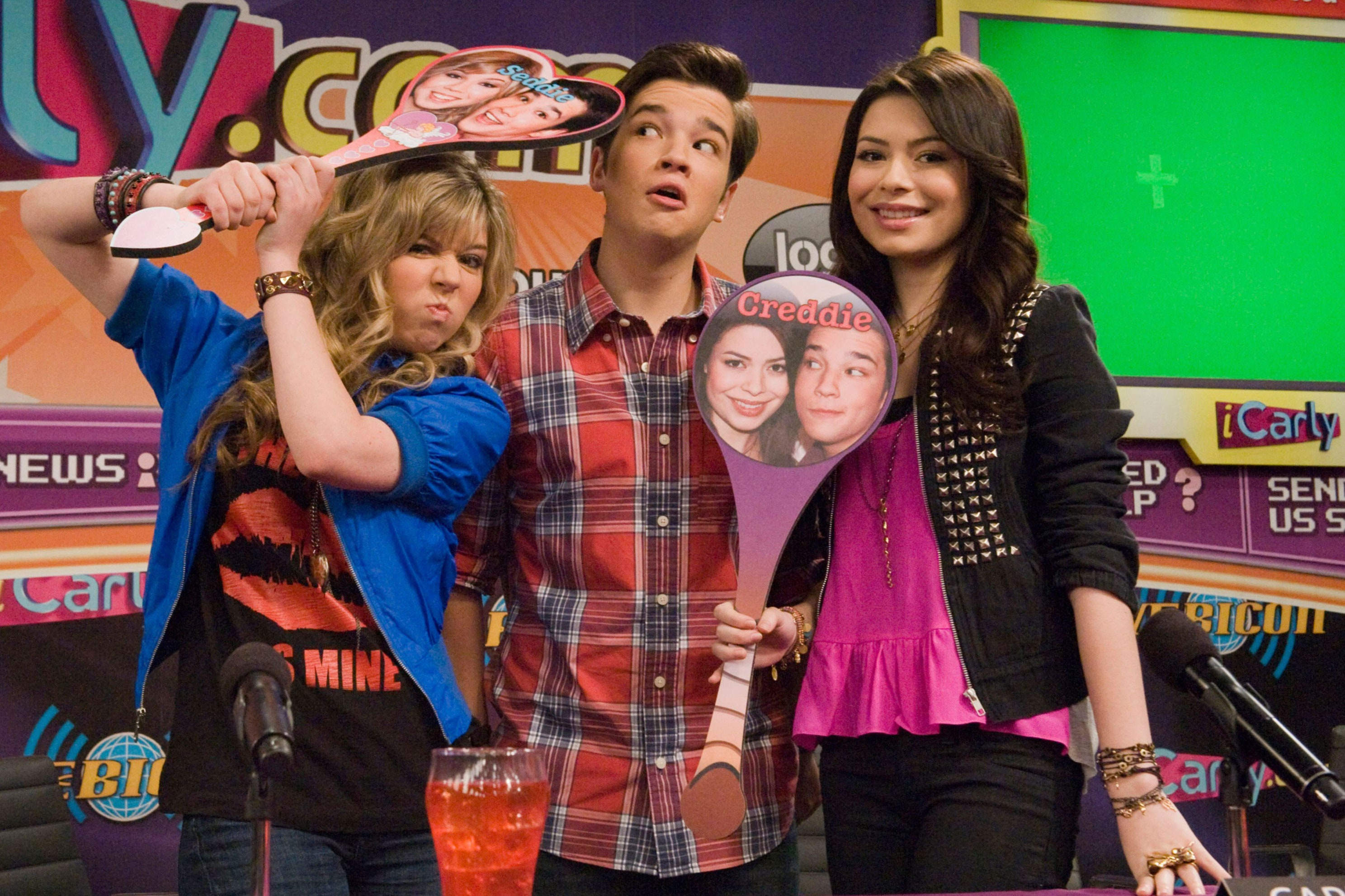 sam, freddie, and carly holding signs with their ship faces on it
