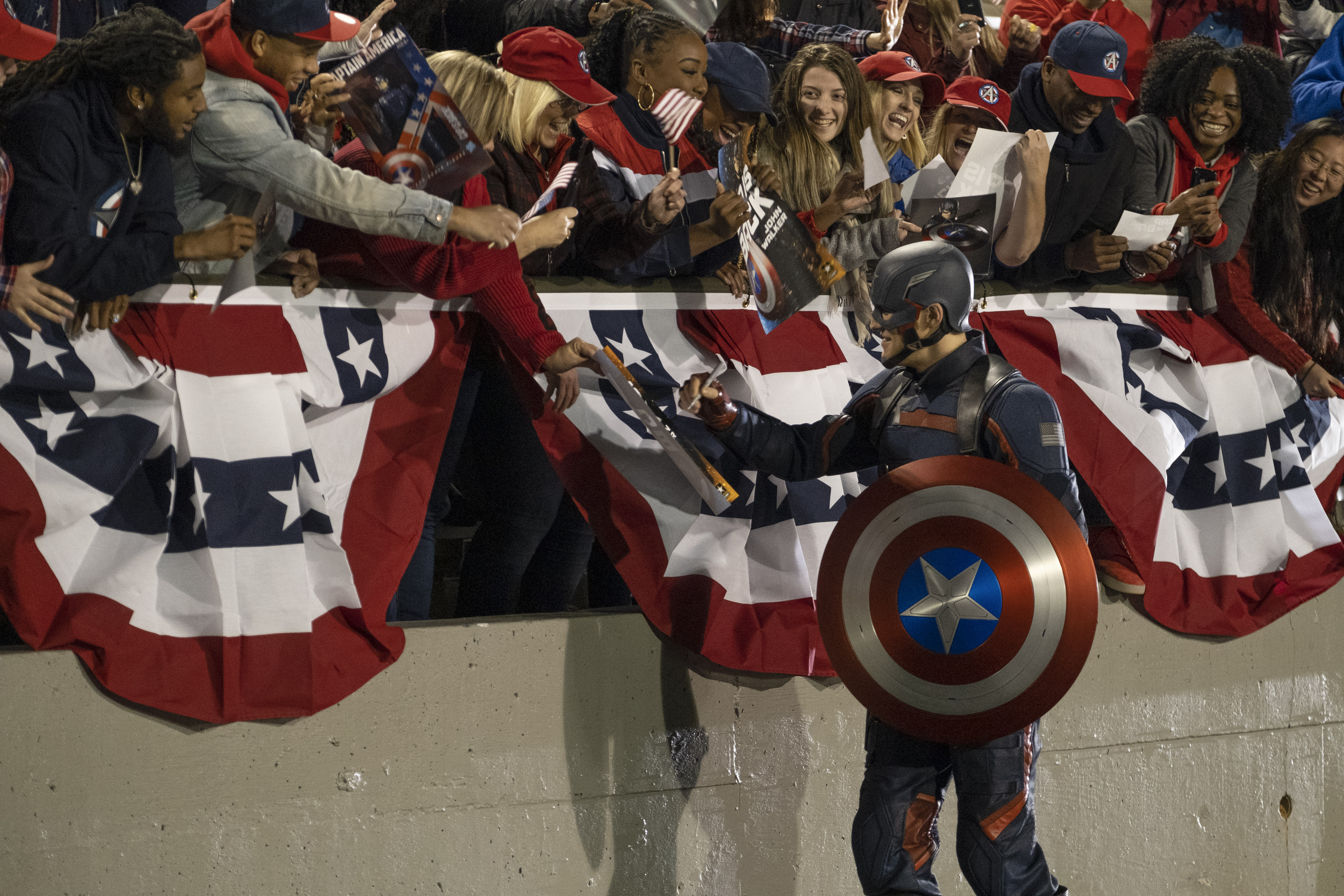 The new Captain America, John Walker, signs autographs at a rally in The Falcon and the Winter Soldier
