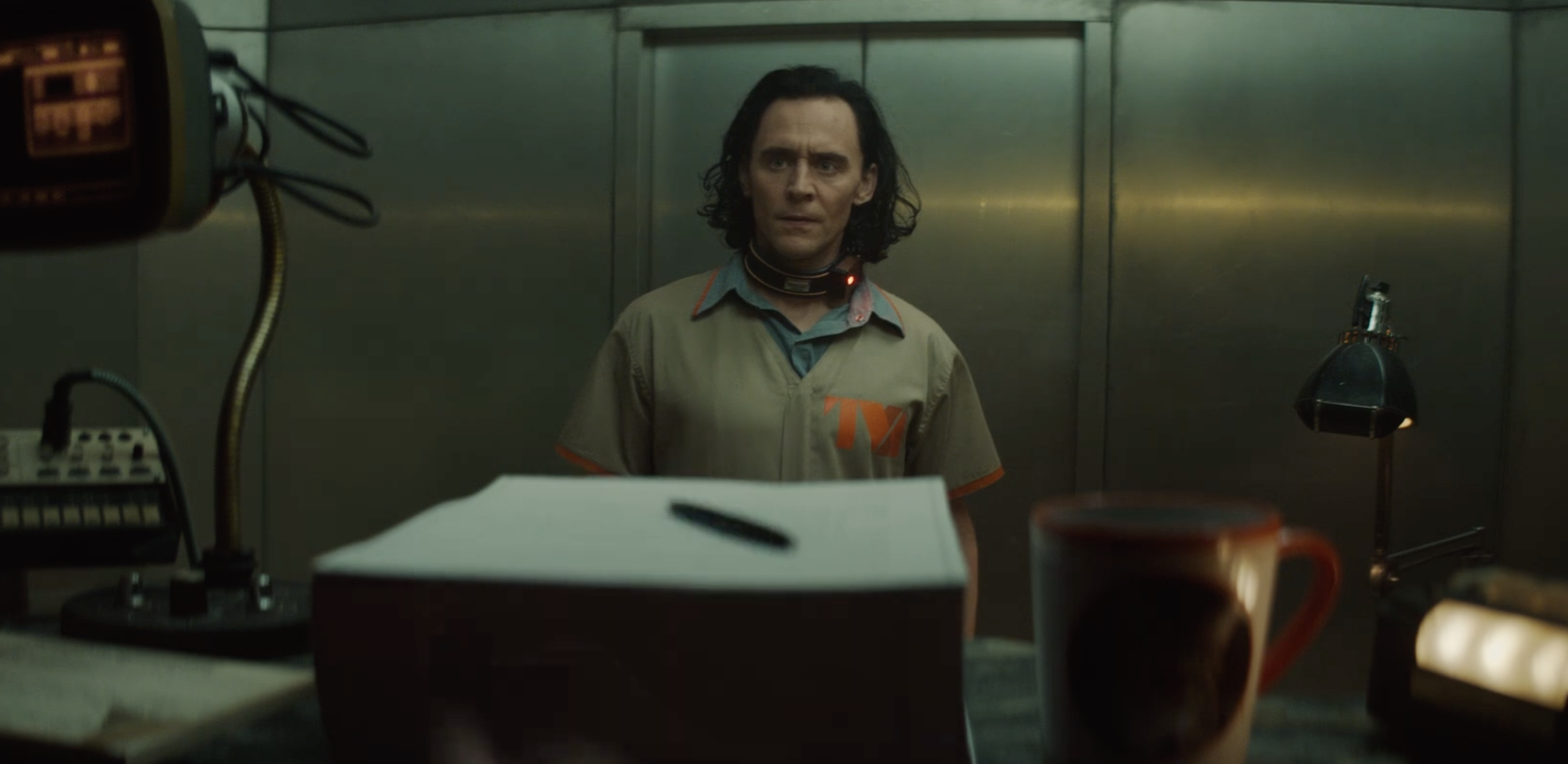 Loki faces a computer screen in a TVA prison jumpsuit from Loki on Disney Plus