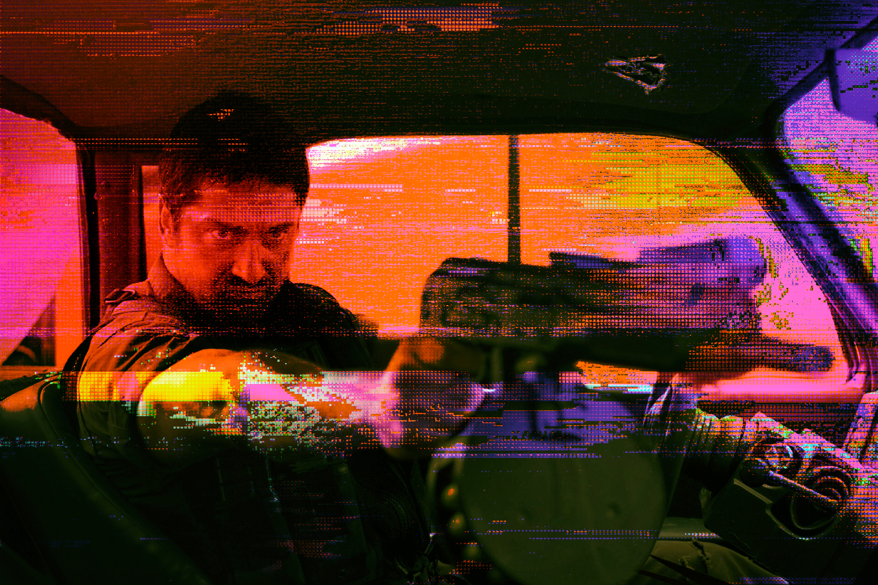 Glitchy, brightly colored image of actor Gerard Butler pointing a large gun in Gamer