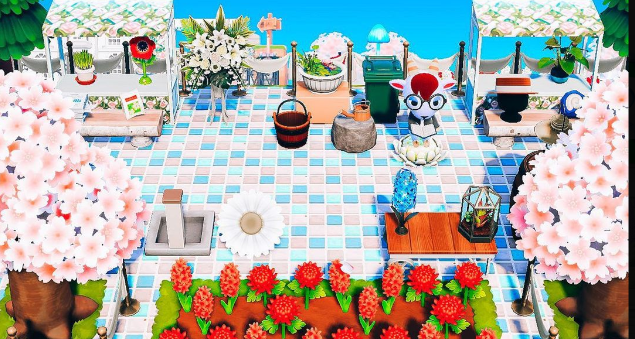 Animal Crossing - a goat villager sits in the middle of an impeccable decorated patio in the sunlight.