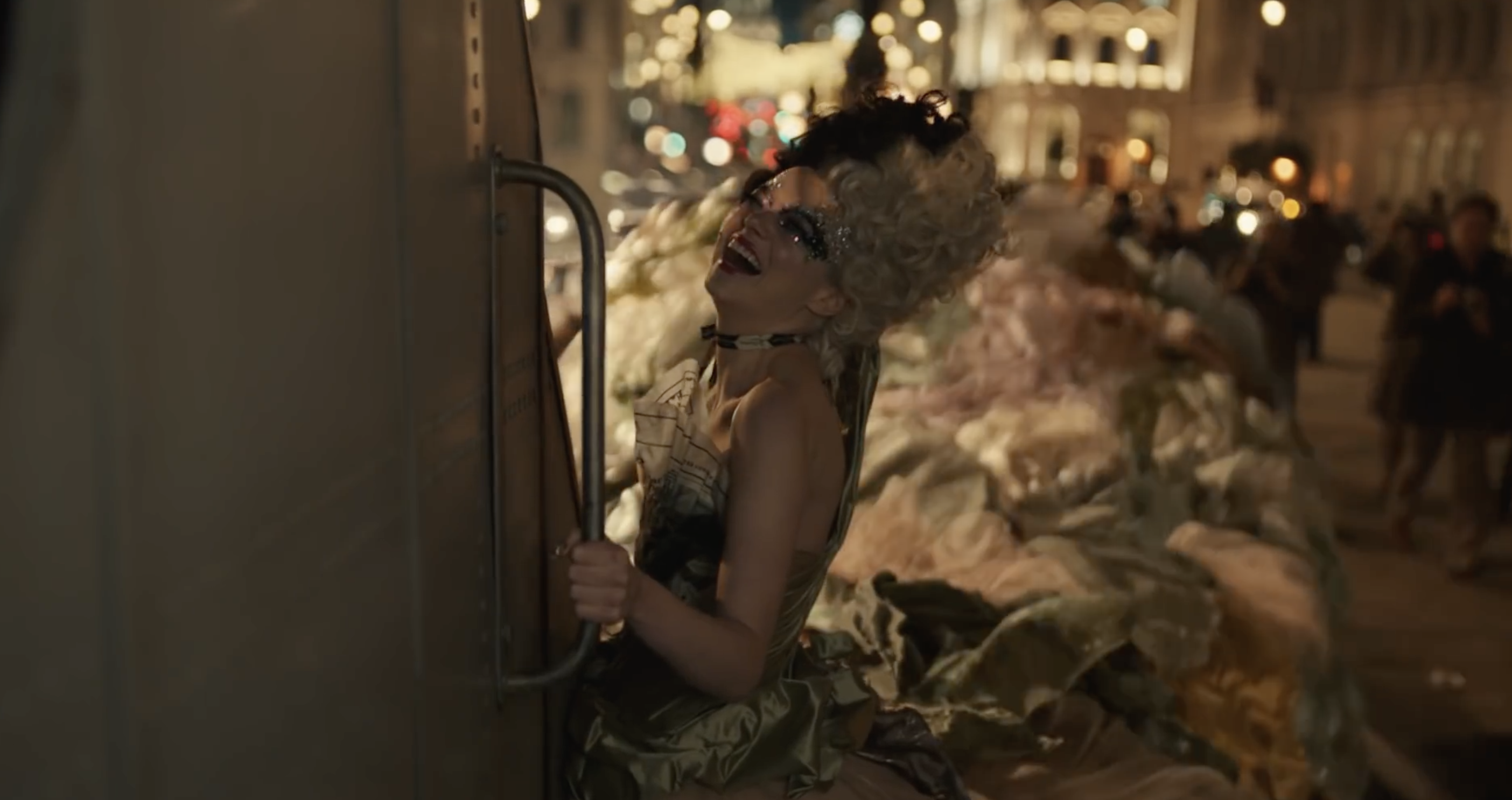 cruella de vil clinging to the back of a truck while wearing a ballgown