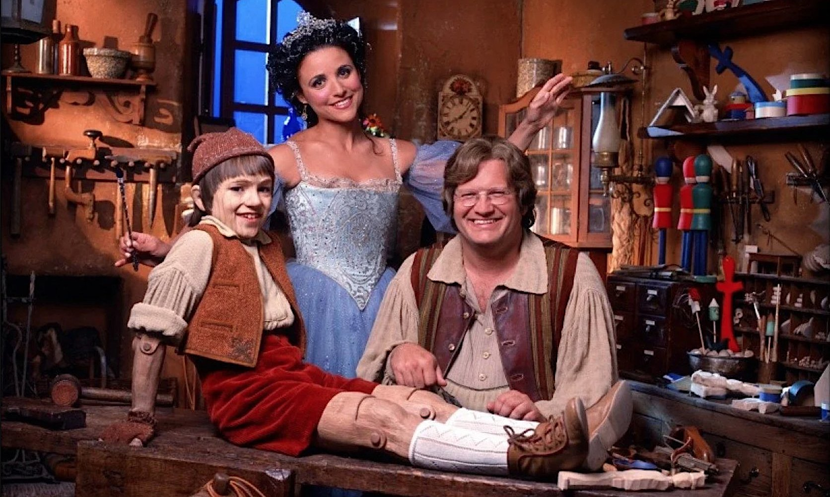 Drew Carey and Julia Louis-Dreyfus beam over the wooden boy Pinocchio in a promo still for 2000's Geppetto