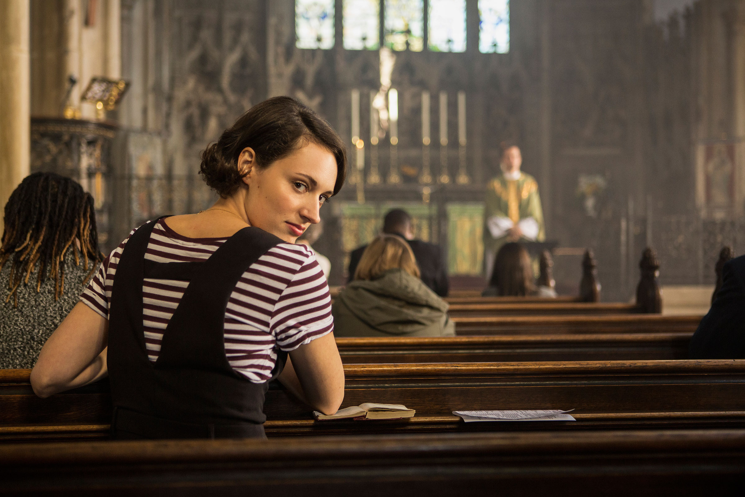Fleabag (Phoebe Waller-Bridge) casts a knowing glance back over her shoulder as she sits in a pew of a church, listening to a service.