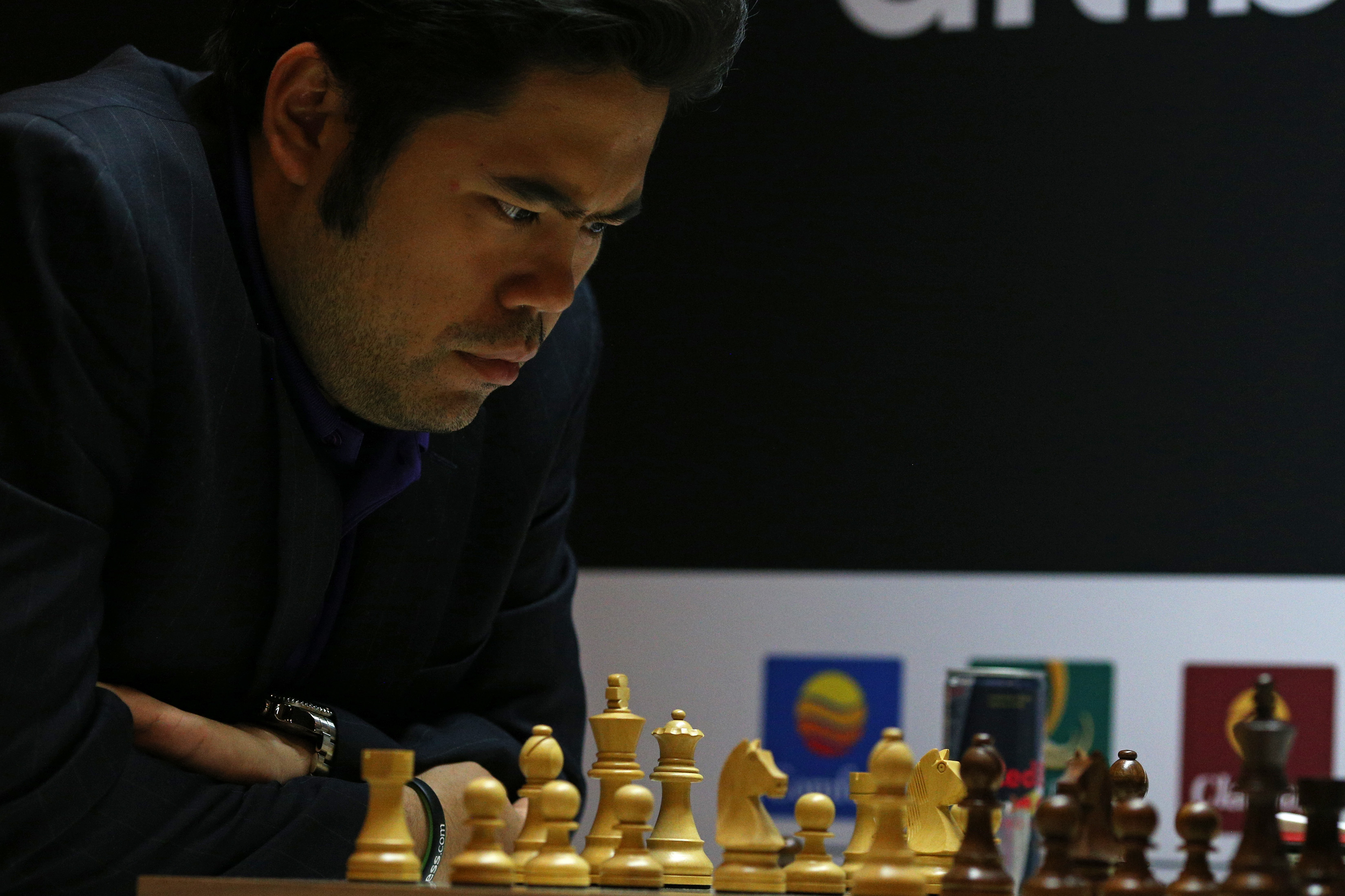 Hikaru Nakamura gazes at a chess board
