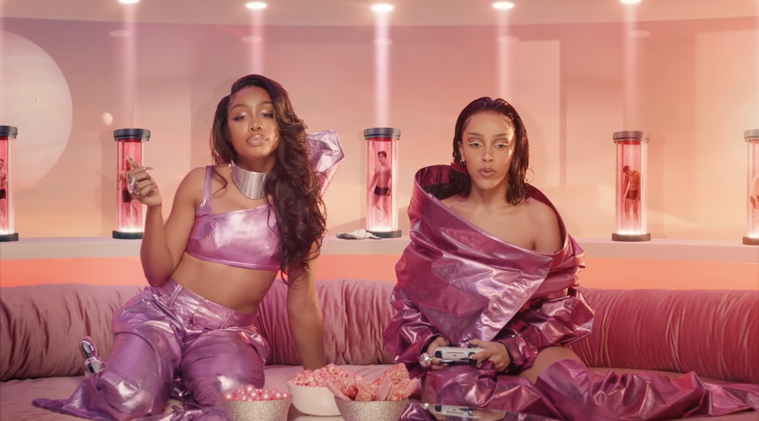 Doja Cat and SZA sitting on a couch, wearing shiny pink outfits while playing video games .