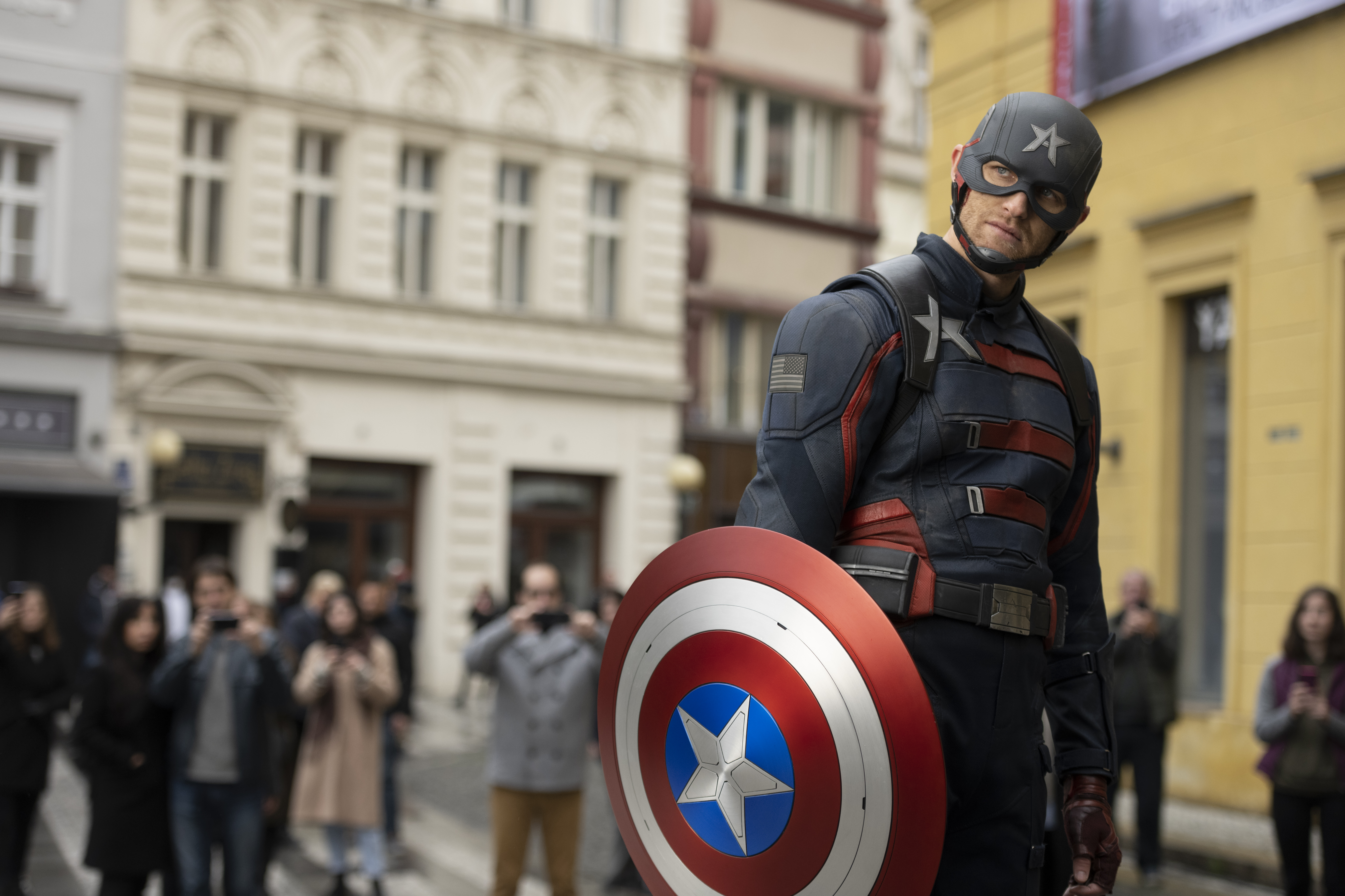 John Walker, the new Captain America in The Falcon and the Winter Soldier, looks askance at the aghast crowd around him