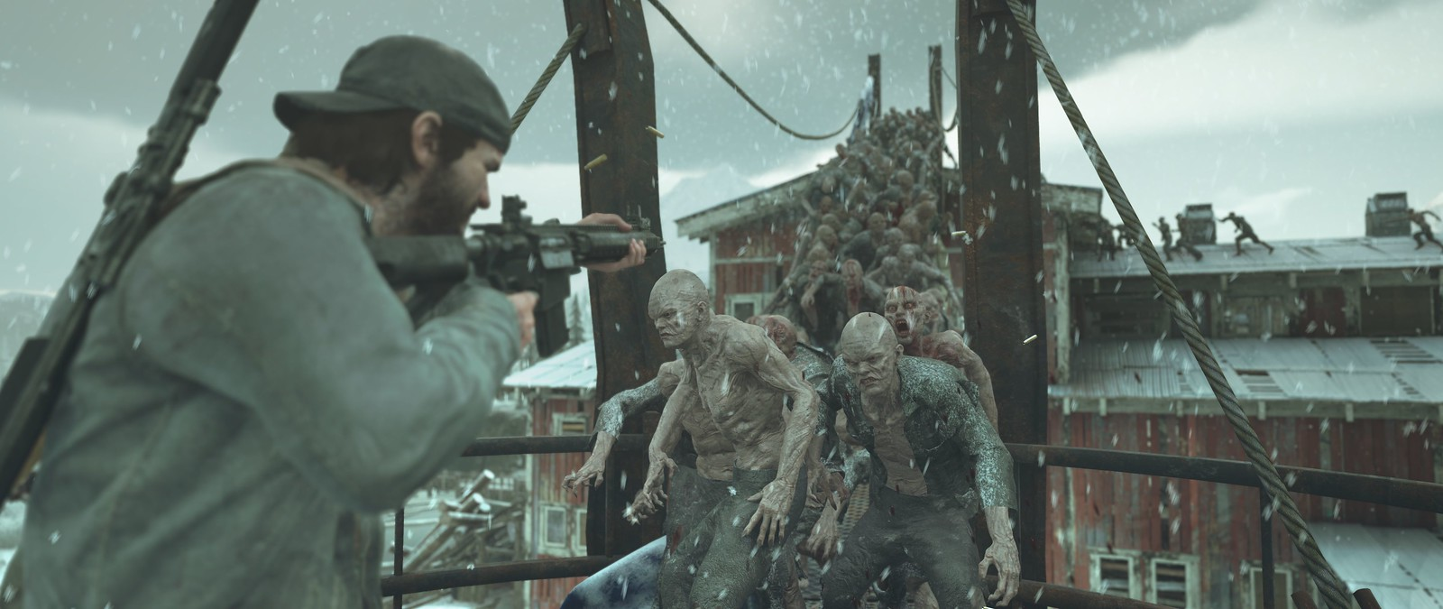 a man aims a rifle at a bunch of zombies coming toward him in Days Gone
