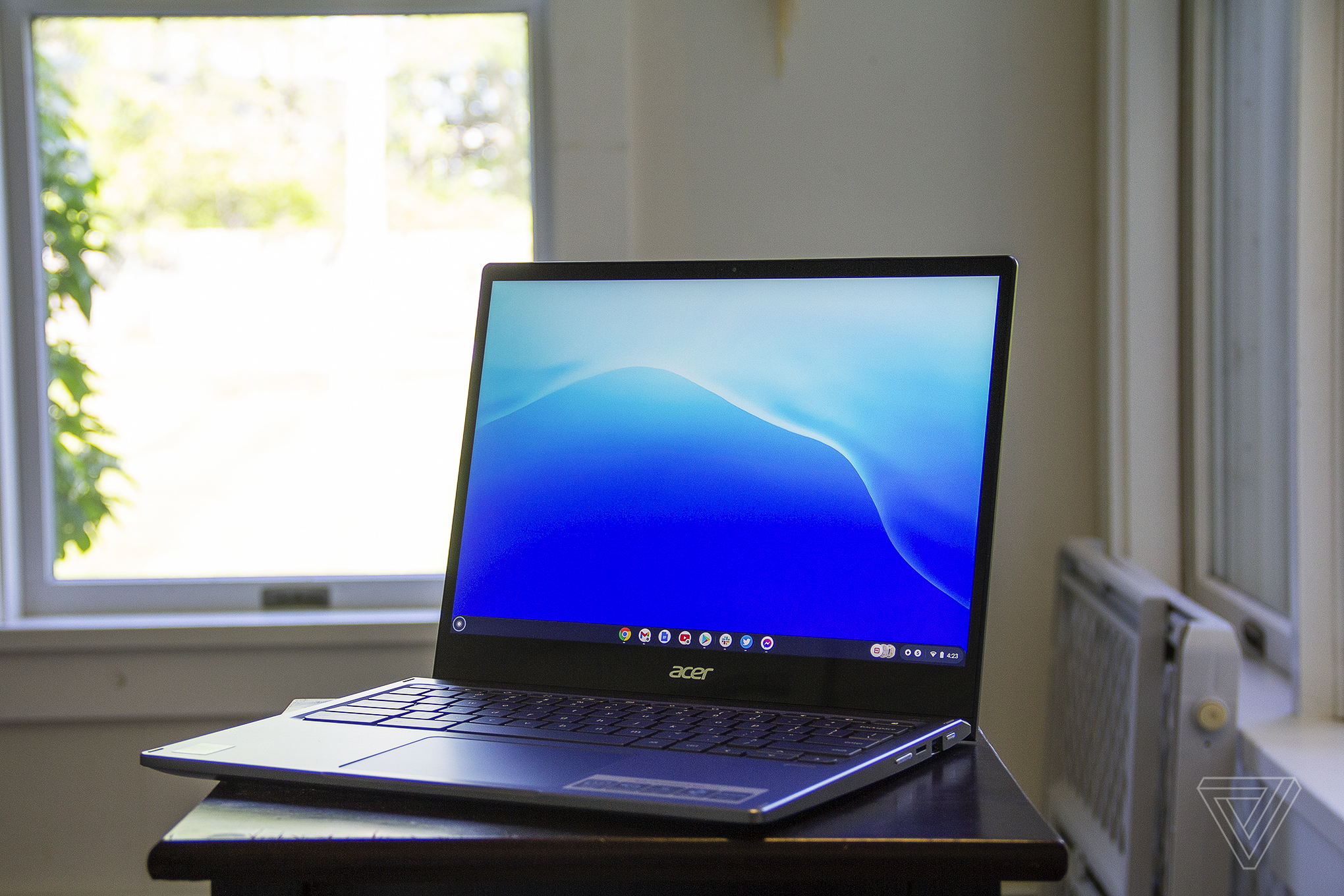 The Acer Chromebook Spin 713 on a small table in front of a bright window. The screen displays a blue pattern.