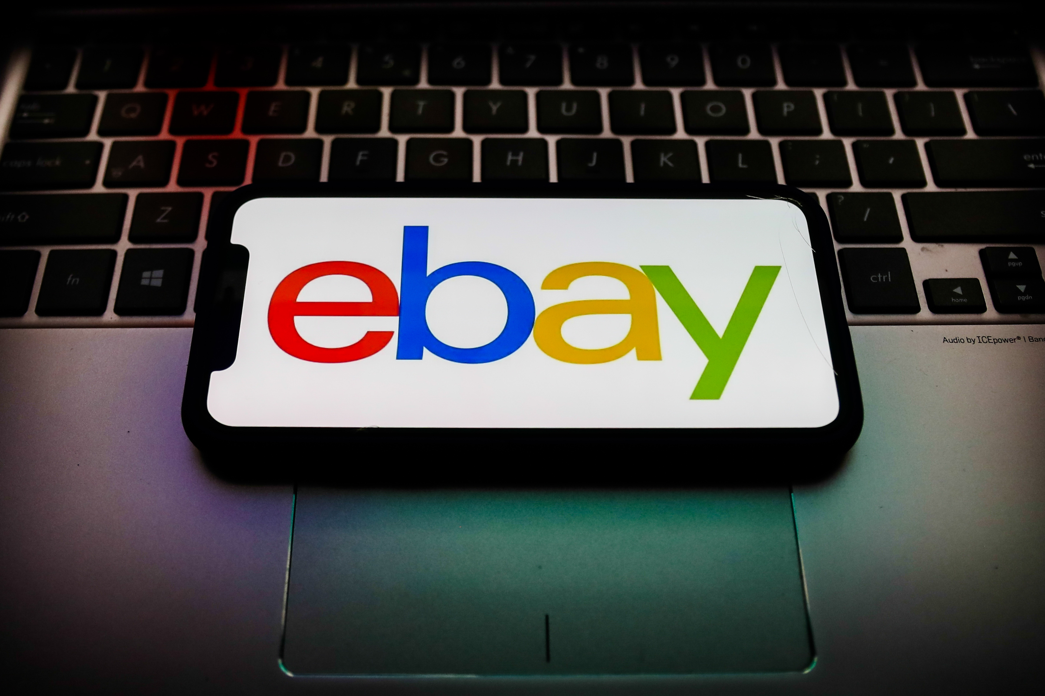 Photo of a phone showing the eBay logo, set on top of a laptop keyboard.