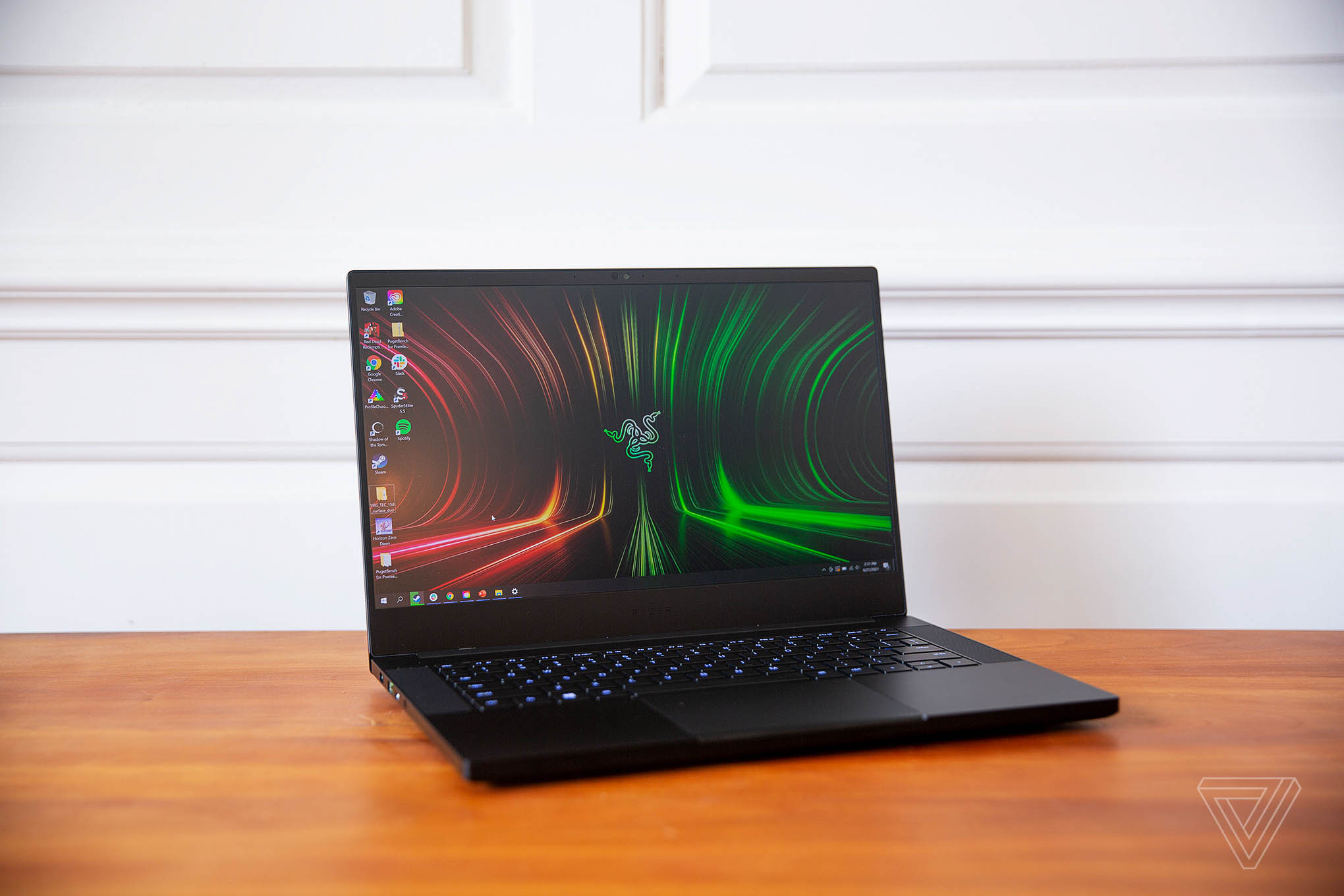 The Razer Blade 14 open, facing the camera, angled to the right. The screen displays the Razer logo on a red and green background.