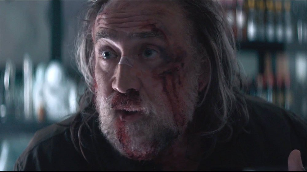Nicolas Cage with a disheveled beard covered in blood in the movie Pig.