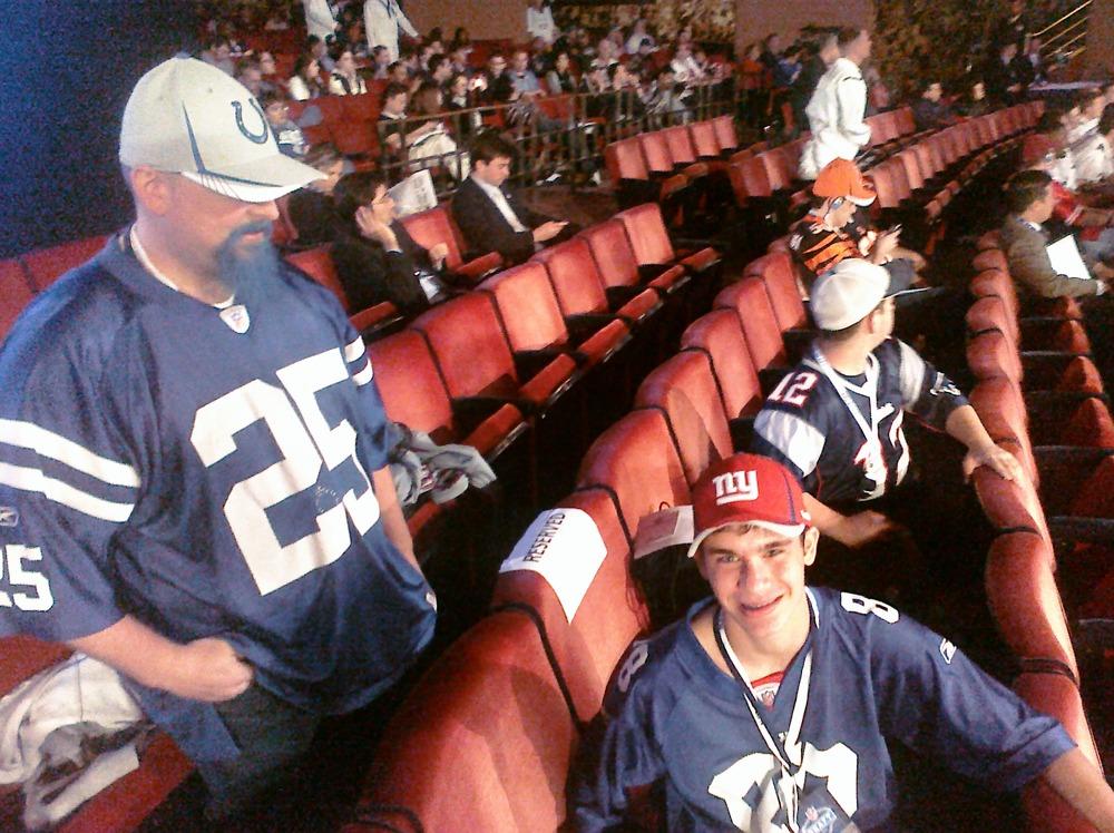 Colts fan and Giants fan smile, Patriots fan in background frowns.