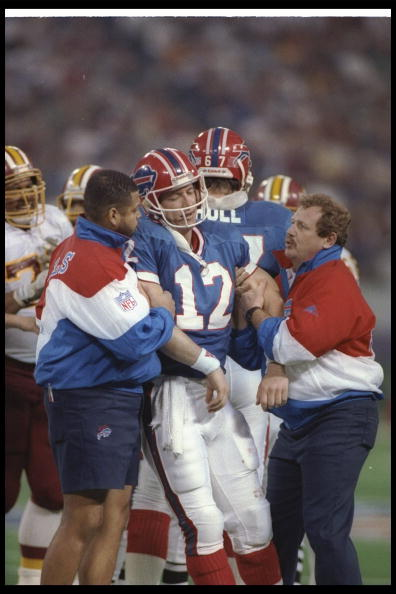 Quarterback Jim Kelly of the Buffalo Bills is helped off the field during Super Bowl XXVI against the Washington Redskins at the Hubert H. Humphrey Metrodome in Minneapolis, Minnesota. The Redskins won the game, 37-24.