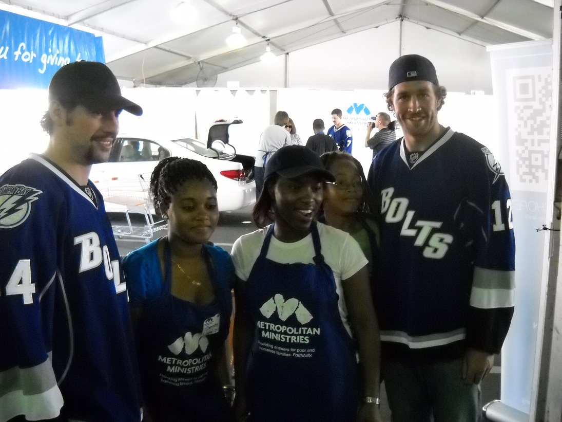 Tampa Bay Lightning players Nate Thompson and Ryan Malone take time out from accepting holiday food donations to visit with volunteers. (photo by Clark Brooks)