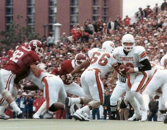 Oklahoma State quarterback Rusty Hilger looks for his running back as the Oklahoma defense closes in during the 1984 Bedlam game. Photo Associated Press.