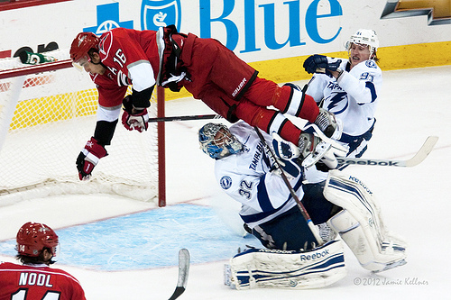 Brandon Sutter sails over goalie Mathieu Garon during overtime in a game between the Carolina Hurricanes and Tampa Bay Lightning on March 3, 2012 (author's photo).