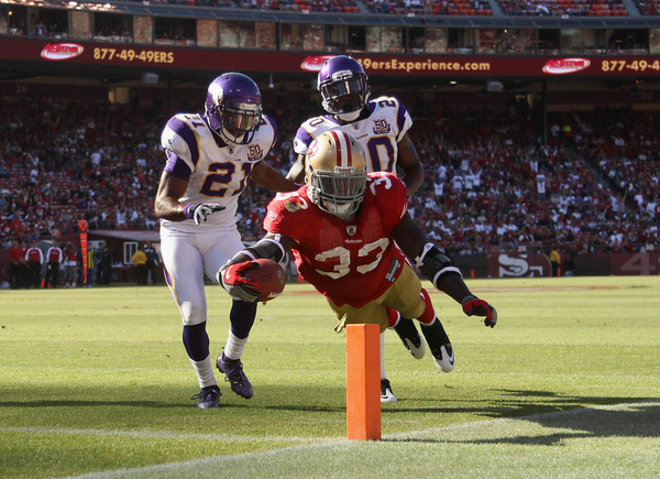 SAN FRANCISCO - AUGUST 22:  Anthony Dixon #33 of the San Francisco 49ers dives past Madieu Williams #20 and Asher Allen #21 of the Minnesota Vikings at Candlestick Park on August 22 2010 in San Francisco California.  (Photo by Ezra Shaw/Getty Images)
