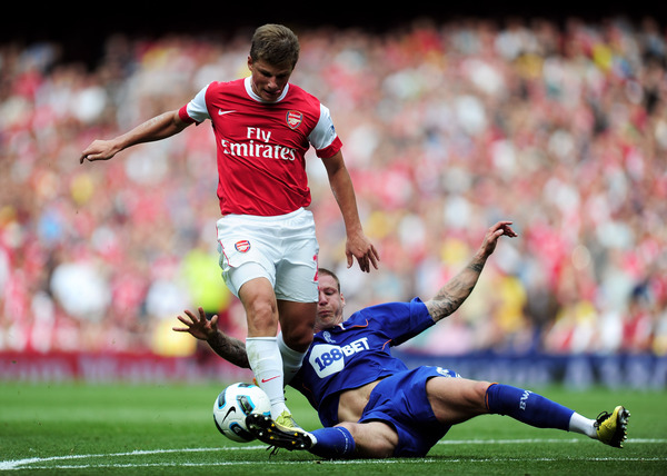 Andrei Arshavin of Arsenal is tackled by Gretar Steinsson of Bolton during the Barclays Premier League match between Arsenal and Bolton Wanderers at The Emirates Stadium in London England. (Photo by Jamie McDonald/Getty Images)