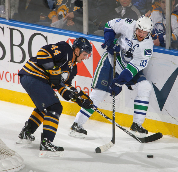 BUFFALO NY - NOVEMBER 15: Andrej Sekera #44  of the Buffalo Sabres and Henrik Sedin #33 of the Vancouver Canucks fight for puck control at HSBC Arena on November 15 2010 in Buffalo New York.  (Photo by Rick Stewart/Getty Images)