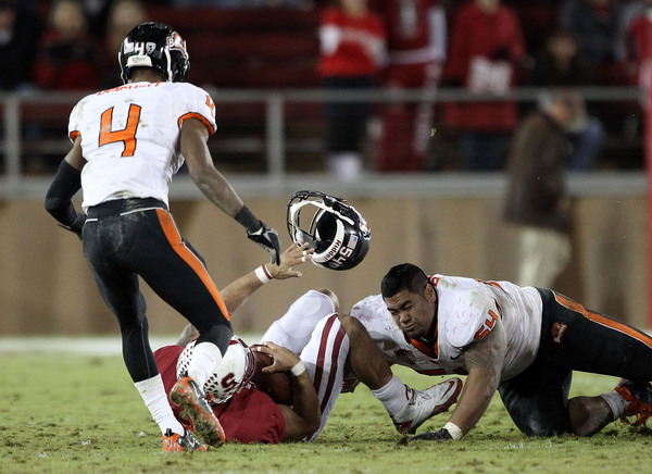 PALO ALTO CA - NOVEMBER 27:  Stephen Paea #54 of the Oregon State Beavers loses his helmet as he tackles Tyler Gaffney #25 of the Stanford Cardinal at Stanford Stadium on November 27 2010 in Palo Alto California.  (Photo by Ezra Shaw/Getty Images)