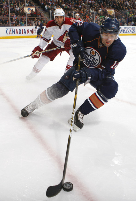 EDMONTON, CANADA - MARCH 17:  Alexandre Giroux #12 formerly of the Edmonton Oilers collects the puck out of the corner against Michal Rozsival #32 of the Phoenix Coyotes(Photo by Dale MacMillan/Getty Images)
