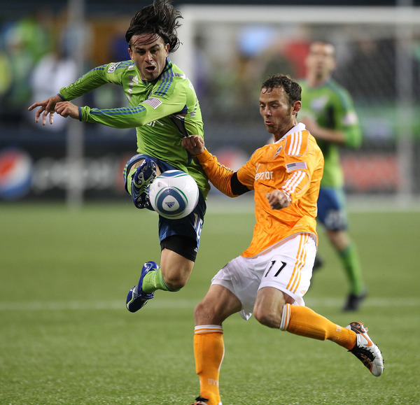 SEATTLE - MARCH 25:  Mauro Rosales #10 of the Seattle Sounders FC battles Brad Davis #11 of the Houston Dynamo at Qwest Field on March 25, 2011 in Seattle, Washington. (Photo by Otto Greule Jr/Getty Images)