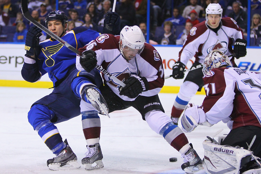 ST. LOUIS, MO - APRIL 5: Chris Stewart #25 of the St. Louis Blues is pushed to the ice by Jonas Holos #36 of the Colorado Avalanche at the Scottrade Center on April 5, 2011 in St. Louis, Missouri.  (Photo by Dilip Vishwanat/Getty Images)