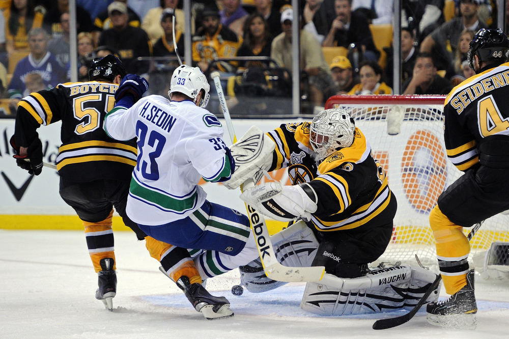 BOSTON, MA - JUNE 06:  Tim Thomas #30 of the Boston Bruins checks Henrik Sedin #33 of the Vancouver Canucks during Game Three of the 2011 NHL Stanley Cup Final at TD Garden on June 6, 2011 in Boston, Massachusetts.  (Photo by Harry How/Getty Images)