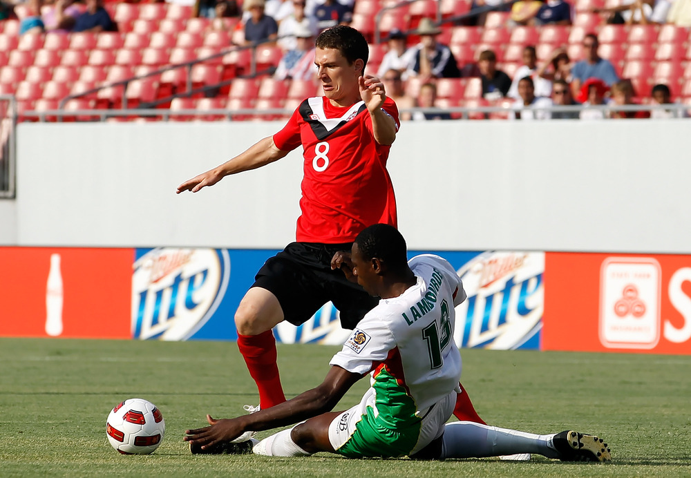 TAMPA, FL - JUNE 11:  Jean-Luc Lambourde #13 of Team Guadeloupe tackles Will Johnson #8 of Team Canada during the CONCACAF Gold Cup Match at Raymond James Stadium on June 11, 2011 in Tampa, Florida.  (Photo by J. Meric/Getty Images)