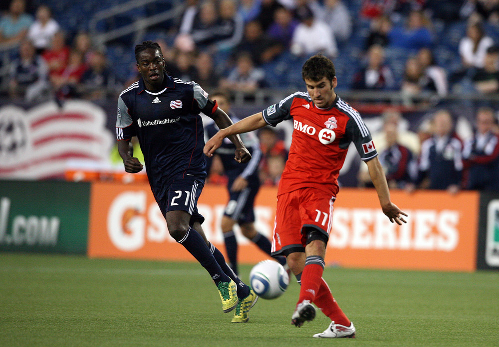 FOXBORO, MA - JUNE 15:  Nathan Sturgis #11 of the Toronto FC keeps the ball away from Shalrie Joseph #21 of the New England Revolution at Gillette Stadium on June 15, 2011 in Foxboro, Massachusetts. (Photo by Gail Oskin/Getty Images)